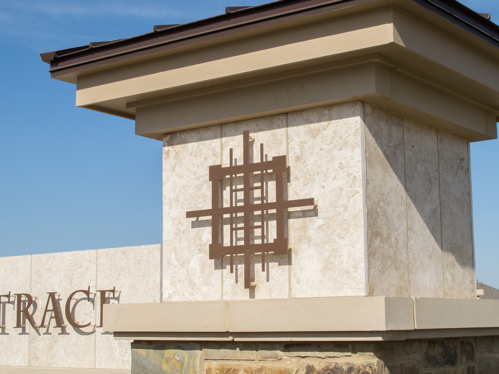 Close up view of dimensional aluminum logo graphics on neighborhood entry monument.