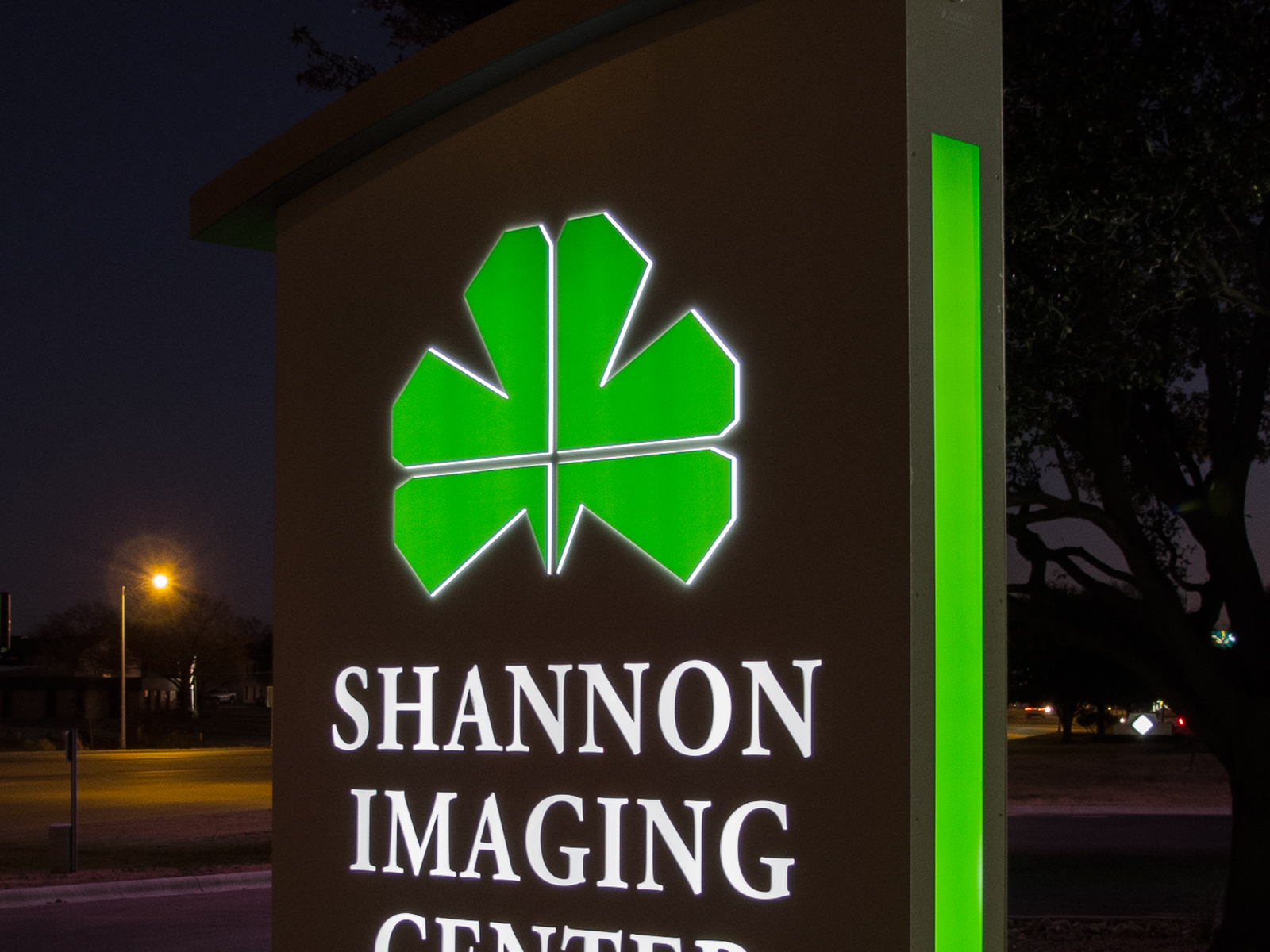 Close up view at night of illuminated push through logo graphics, reverse cut copy, side accents.