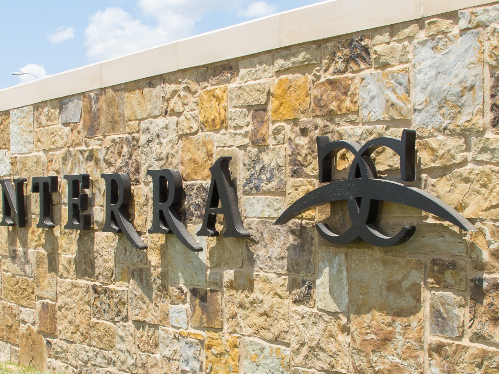 Close up view from side of custom halo-illuminated channel letters and logo graphics mounted to stone monument.