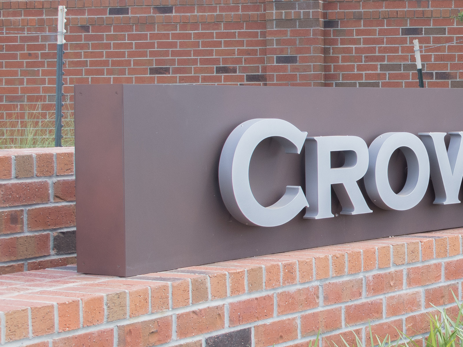 Close up view of custom fabricated, curved aluminum faux-corten sign cabinet with halo-illuminated channel letters.