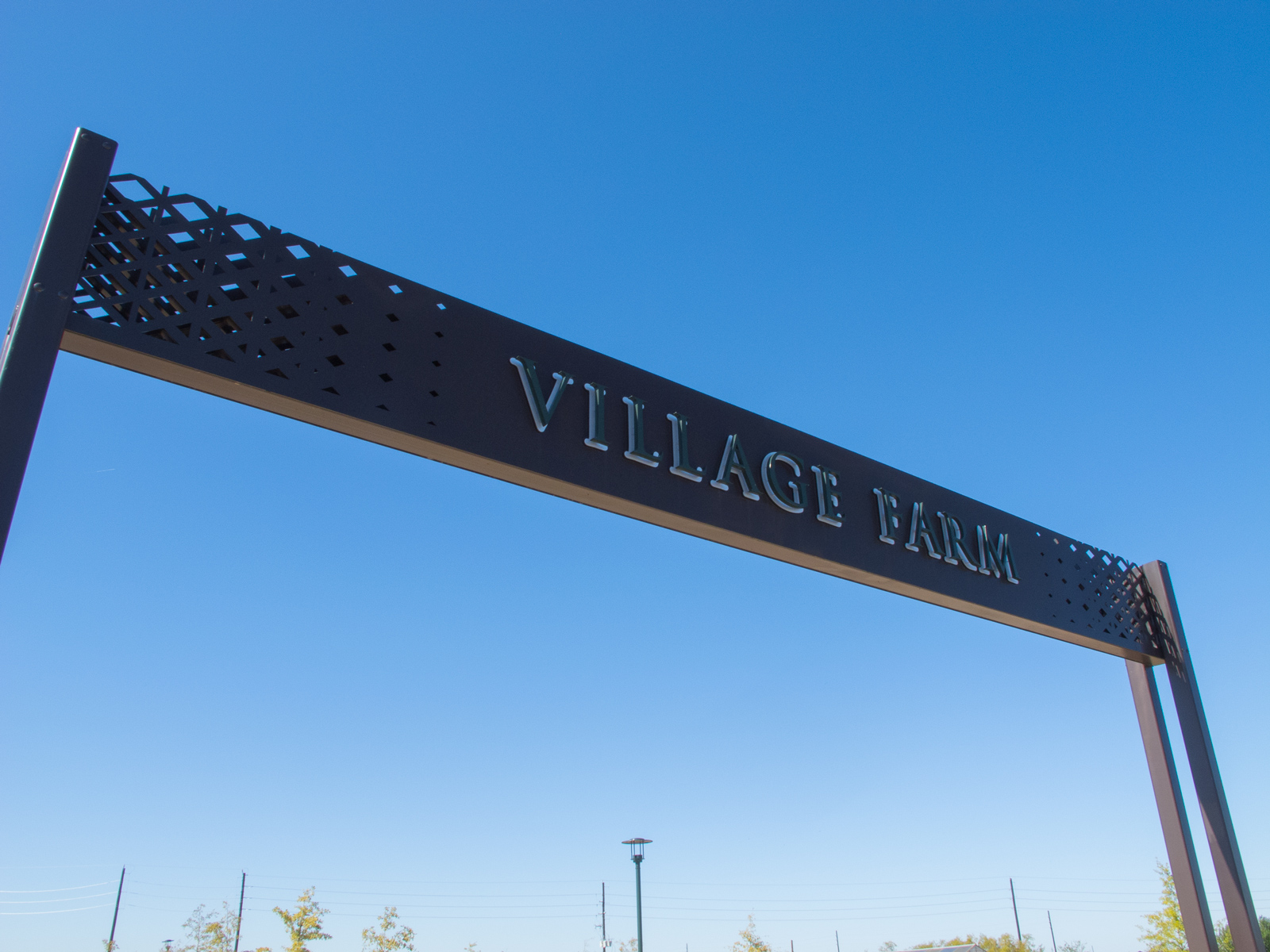 Close up view of custom fabricated, halo-illuminated channel letters with reflection plate for overhead entry signage.