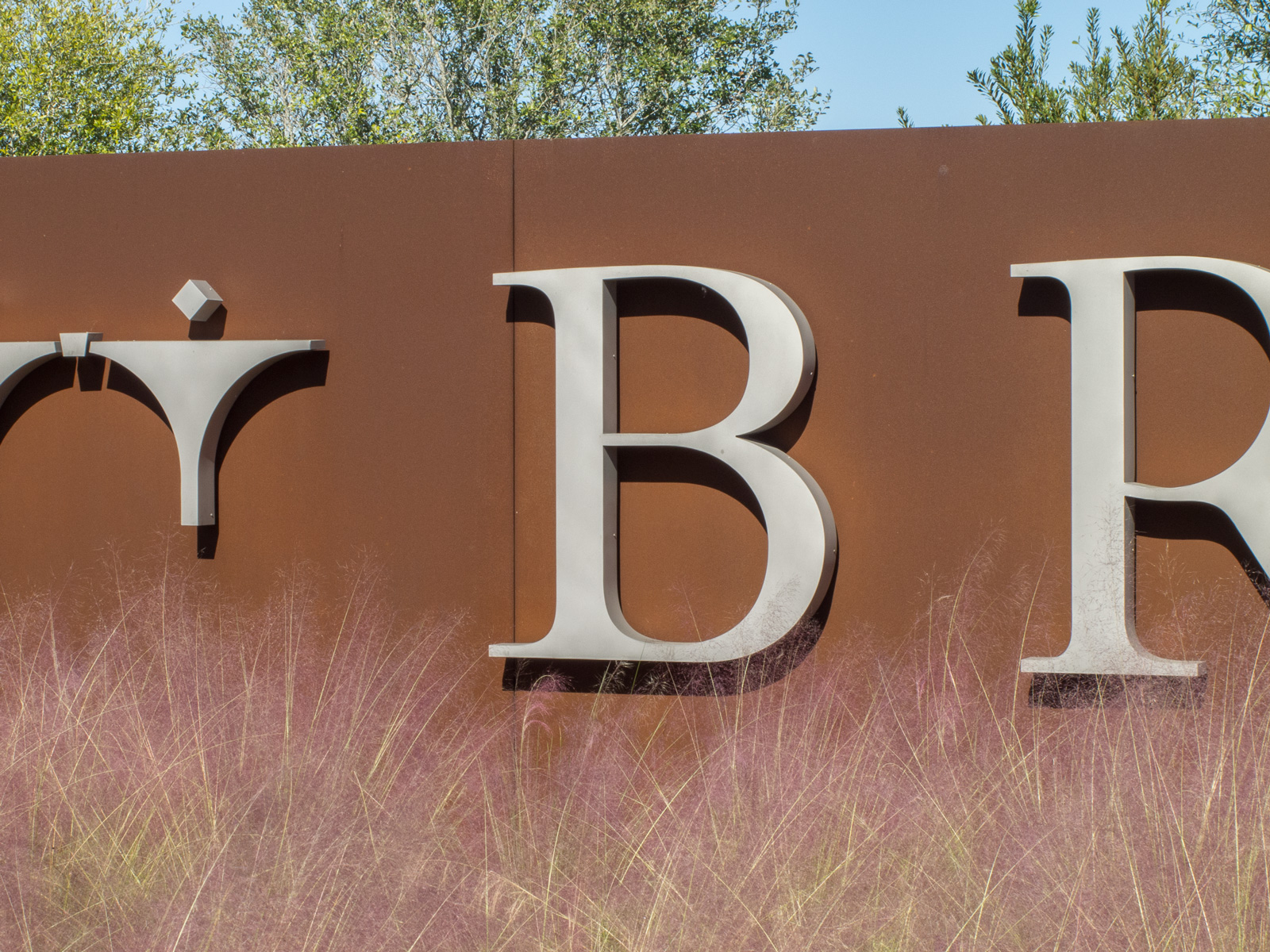 Close up view of stainless steel, halo-illuminated channel letters and roll-formed weathering steel plate sign wall.