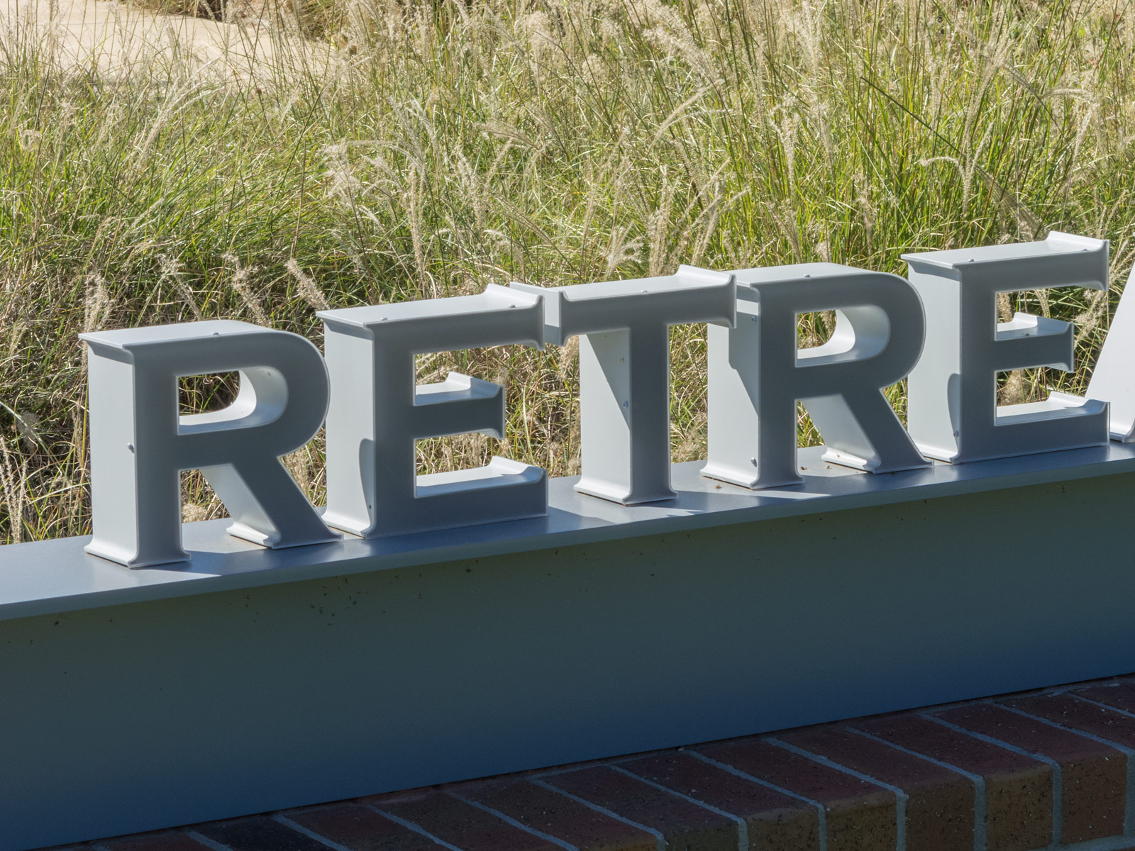 Close up view of fabricated aluminum accent structure with custom, free-standing illuminated channel letters with 3Form faces.