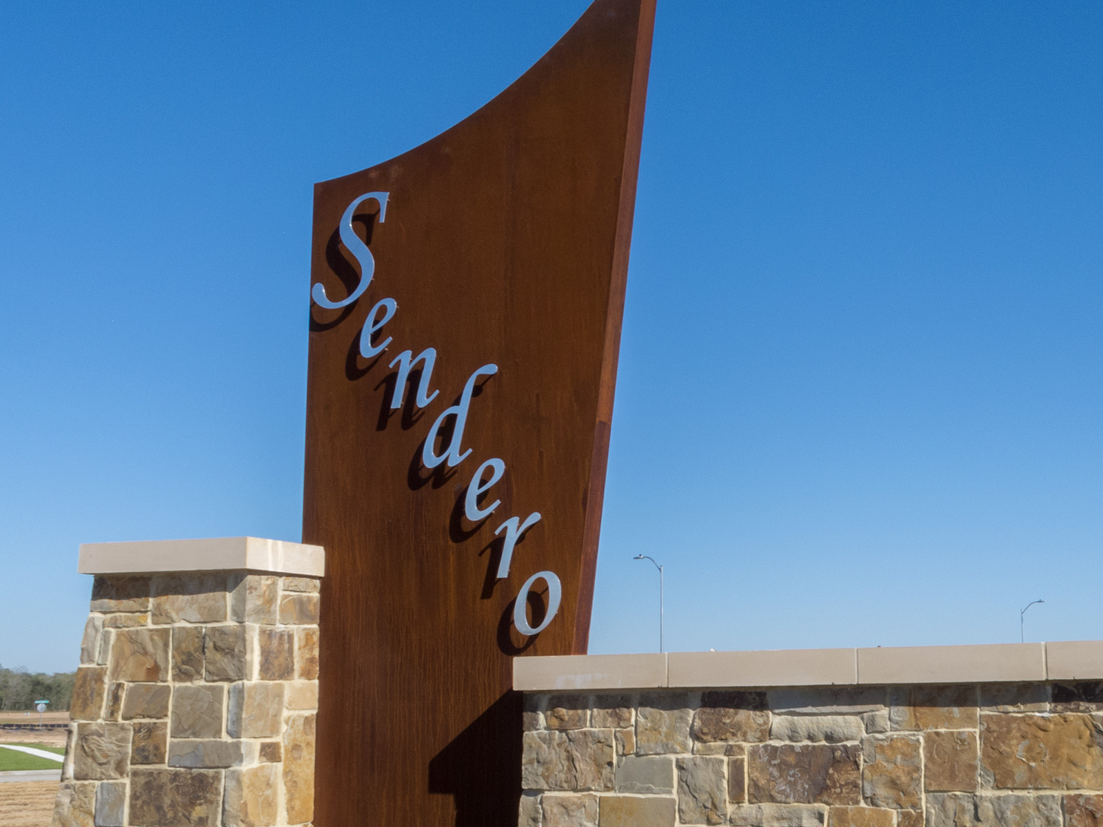 Close up view of custom fabricated, weathering steel sign structure with polished stainless steel dimensional letters.