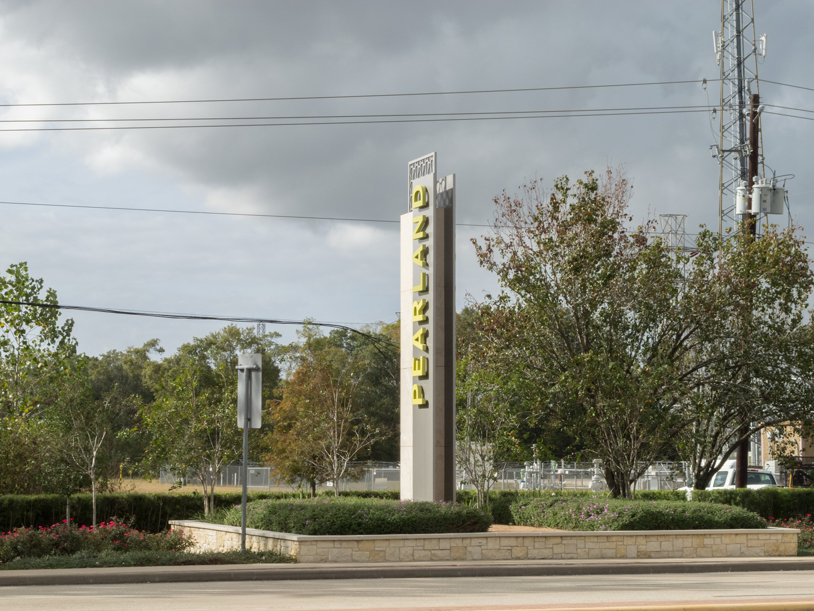 Side view of 24-foot gateway with fabricated aluminum pans, halo-illuminated channel letters, and custom top cap.