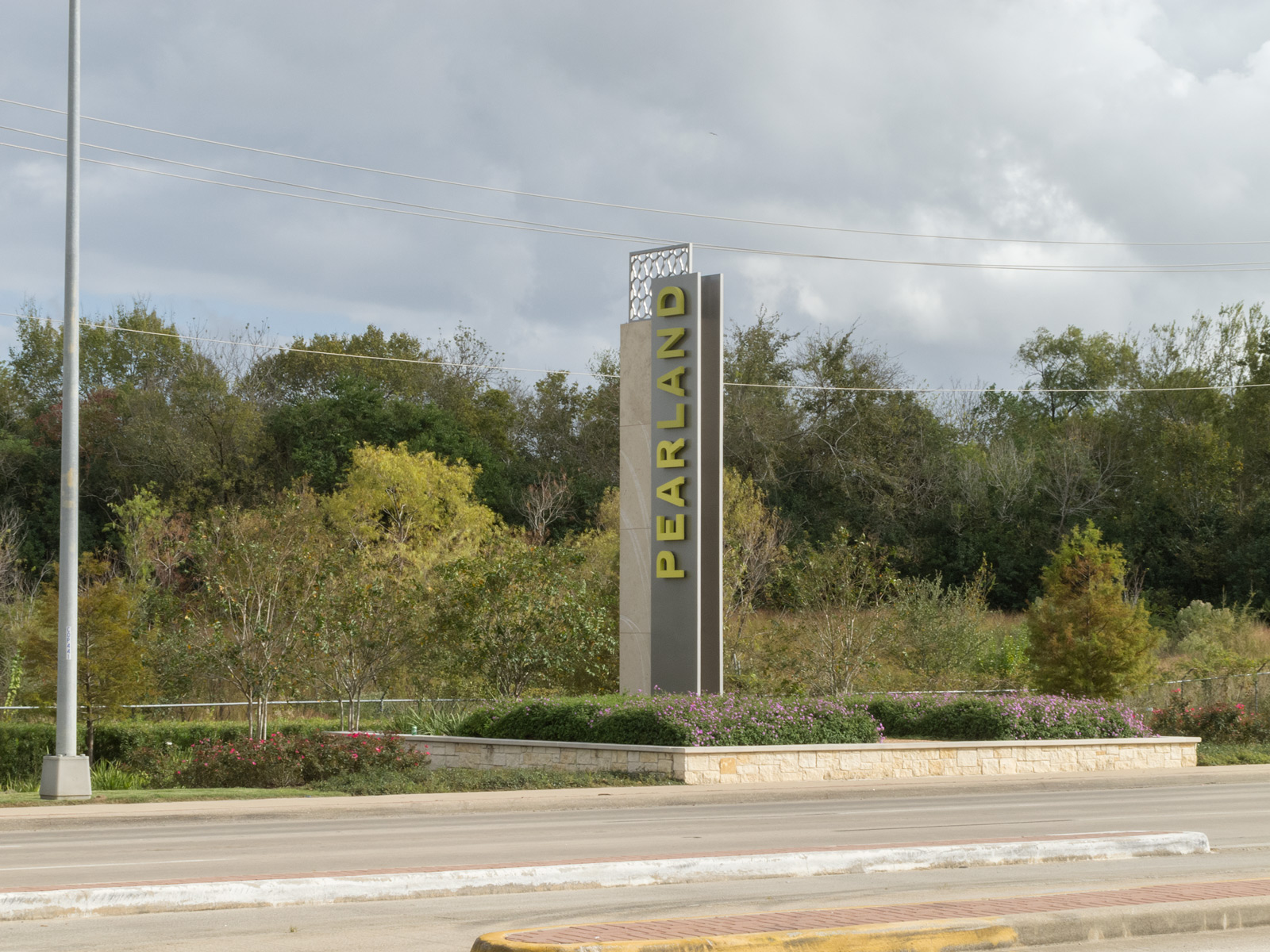 Corner view of 24-foot gateway with fabricated aluminum pans, halo-illuminated channel letters, and custom top cap.