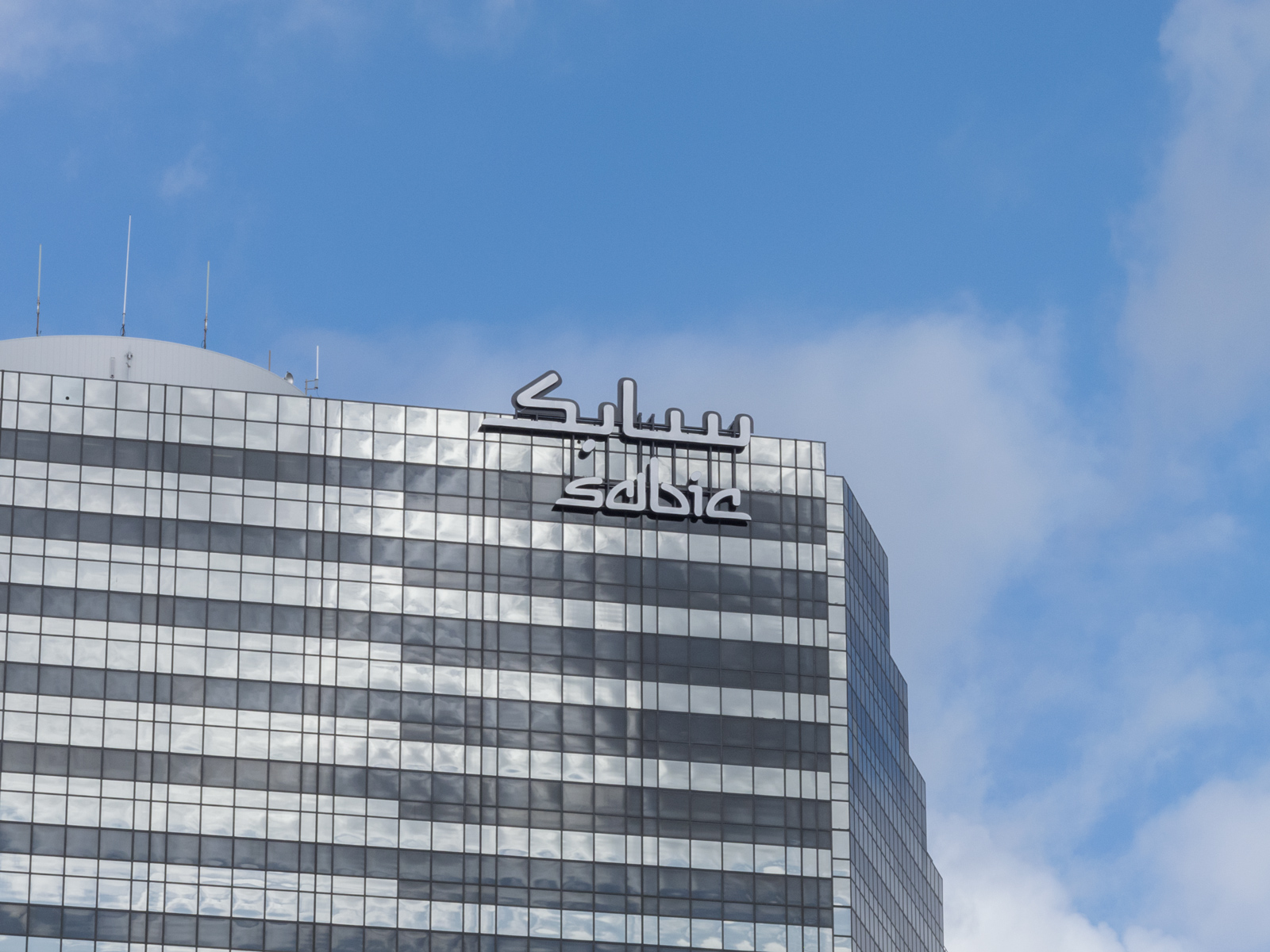 Close up of custom grand scale, face-illuminated channel letters attached to roof of 25-story office tower.