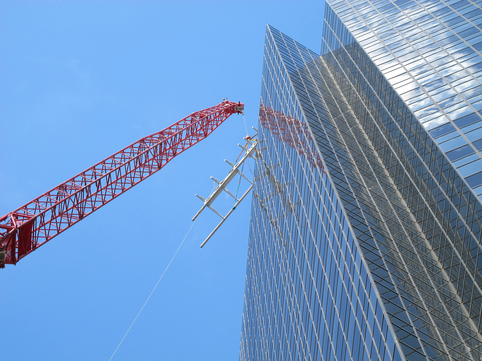 View from ground of crane lifting steel support base structure up to roof of office tower.