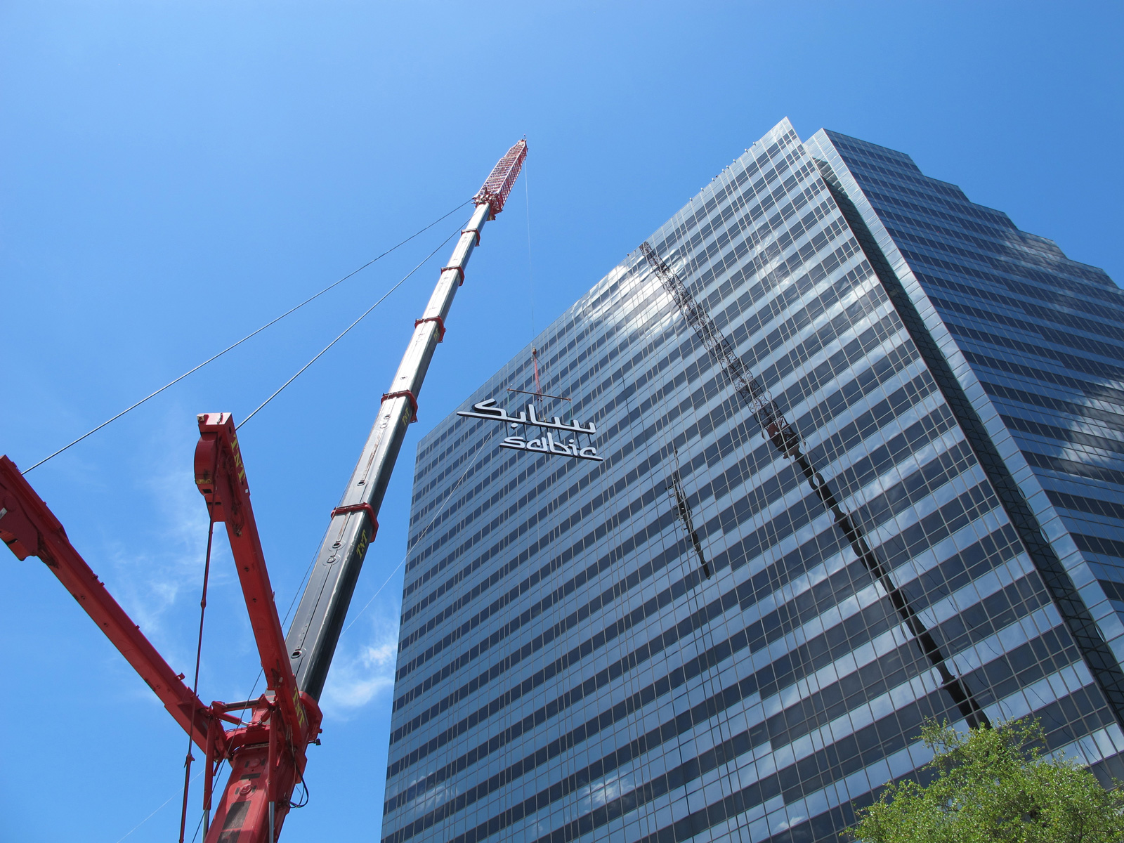 View from ground of crane lifting grand scale face-illuminated channel letters to roof of office tower.