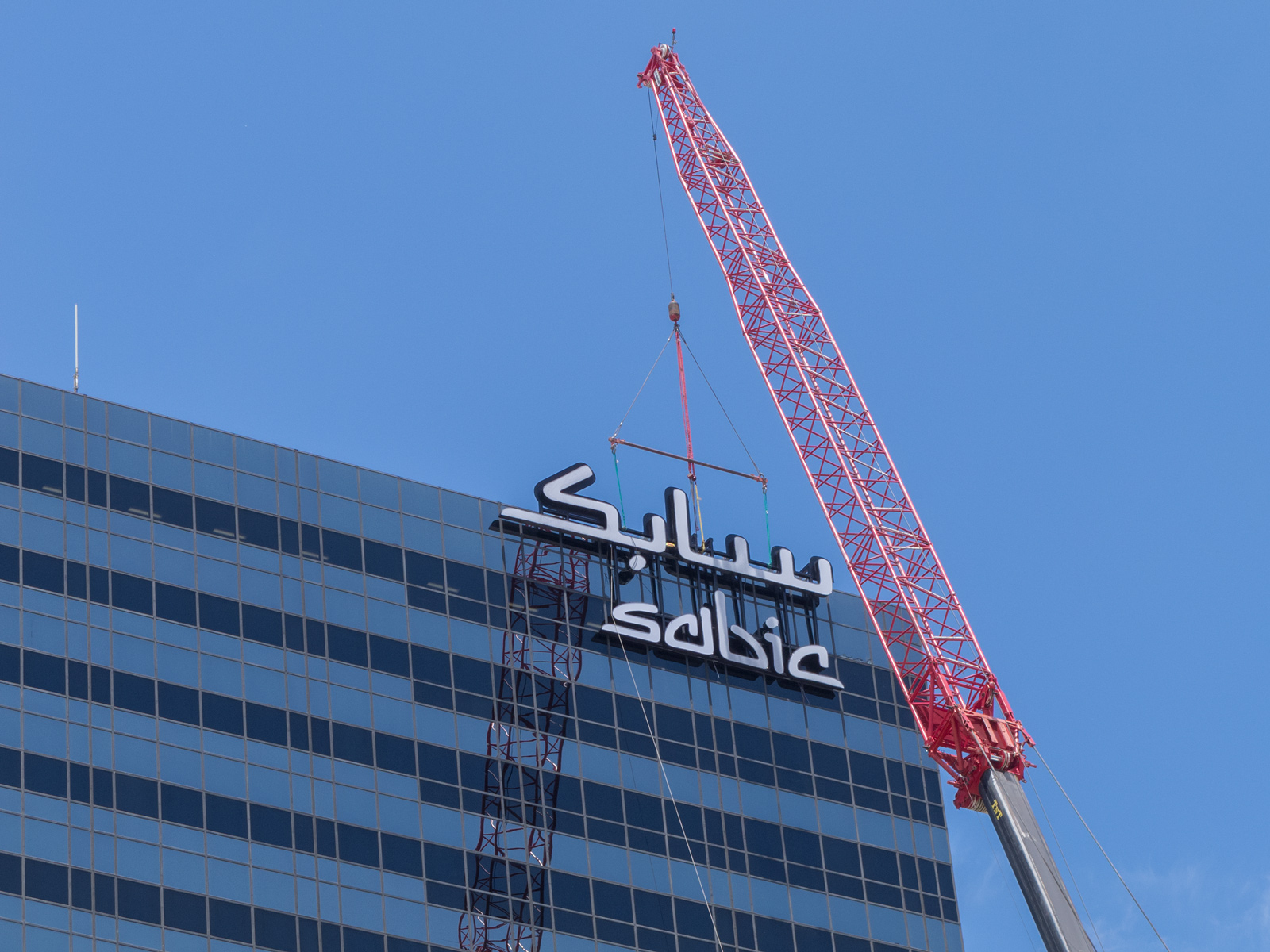 View from ground of crane supporting grand scale channel letters during installation to roof of office tower.