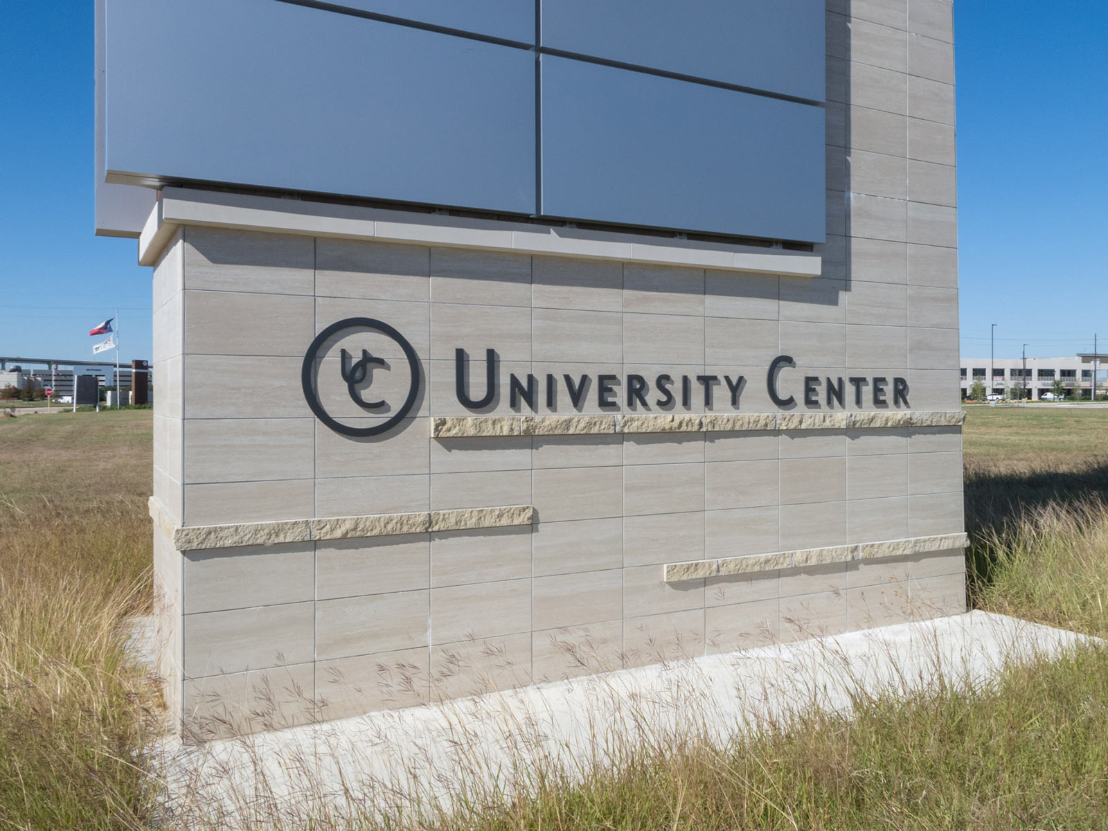 Close up view of dimensional aluminum logo on large-scale multi-tenant monument.