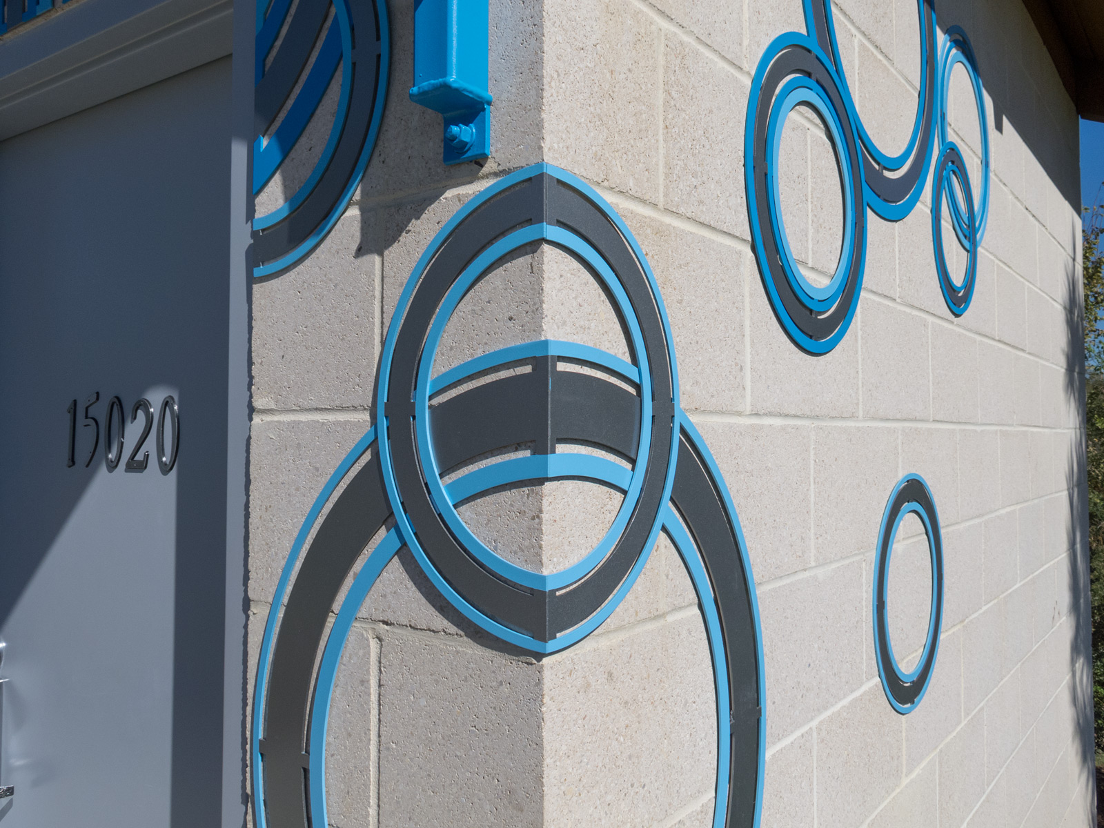 Close up of custom cut, multi-color decorative aluminum rings wrapping corner building.