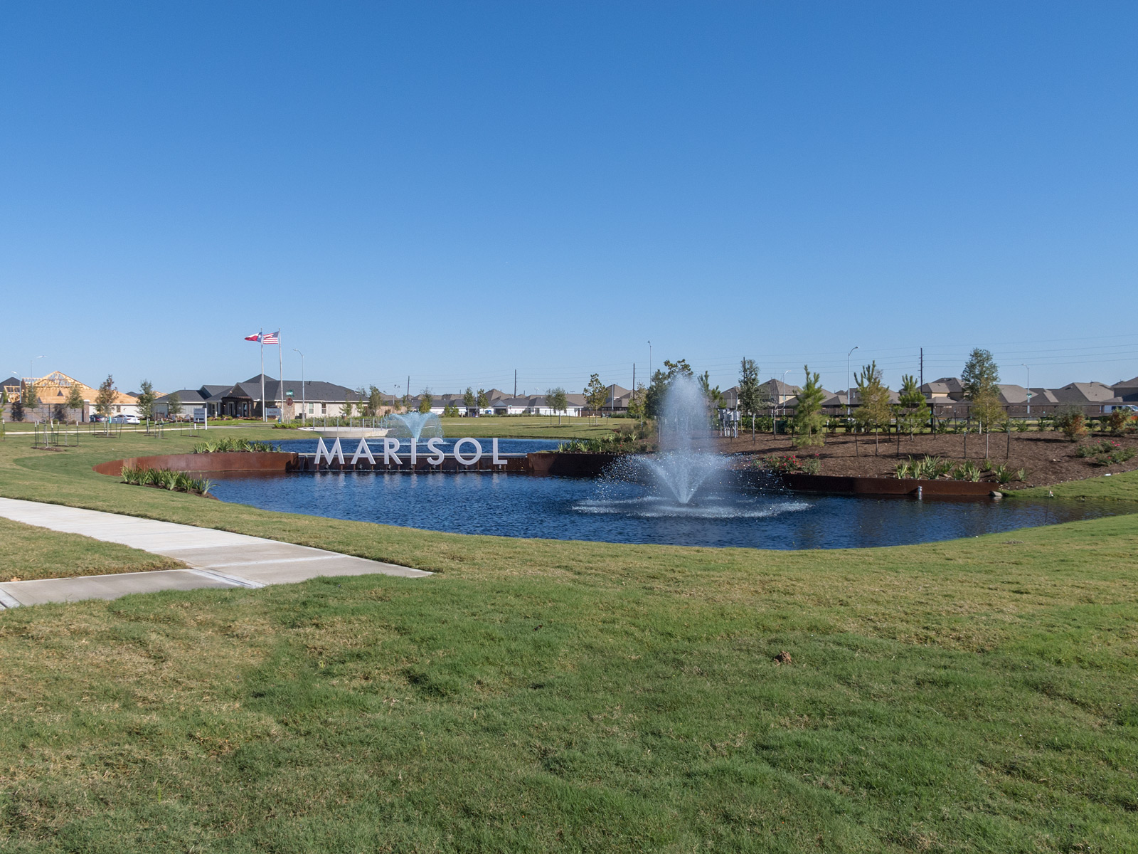 Wide view of fabricated letterforms mounted in pond with custom weathering steel weir wall and retaining walls.