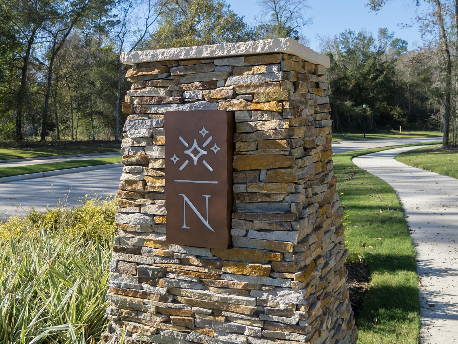 Close up of internally illuminated column sconce with reverse cut graphics at the Northgrove Community.
