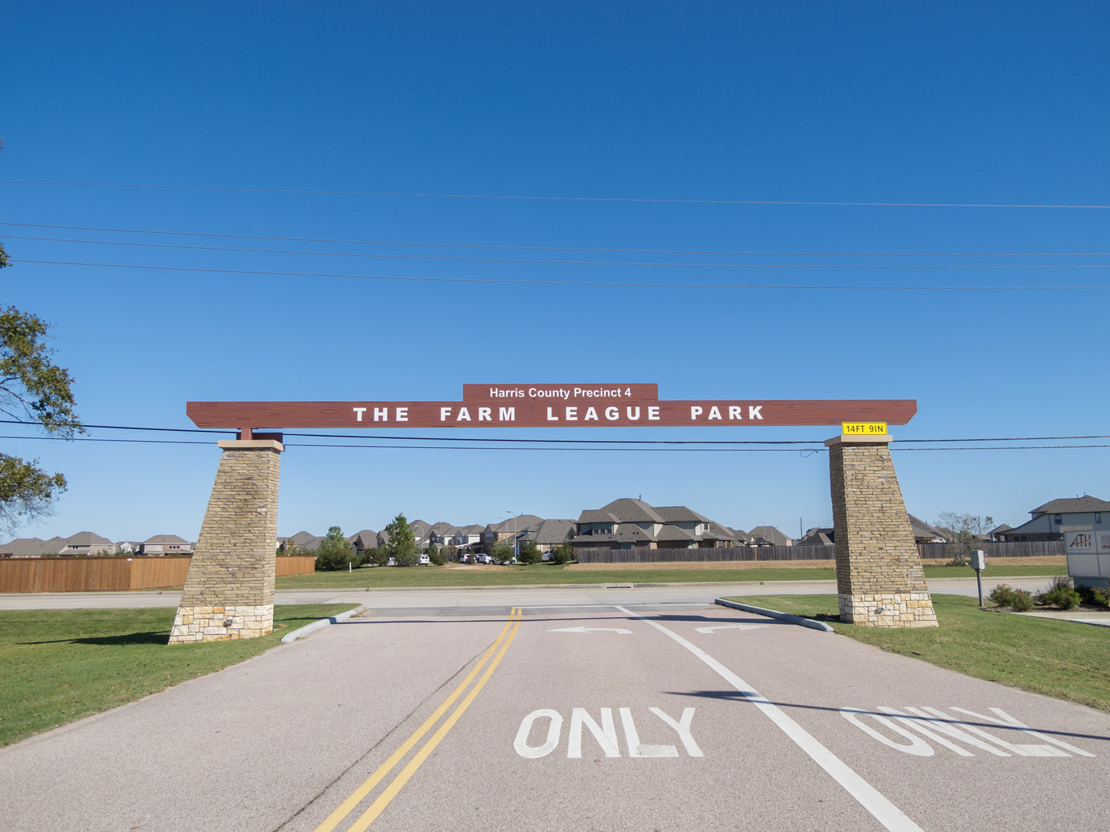 Park gateway with i-beam with engraved wood grain texture and letters and projecting, illuminated cabinets.
