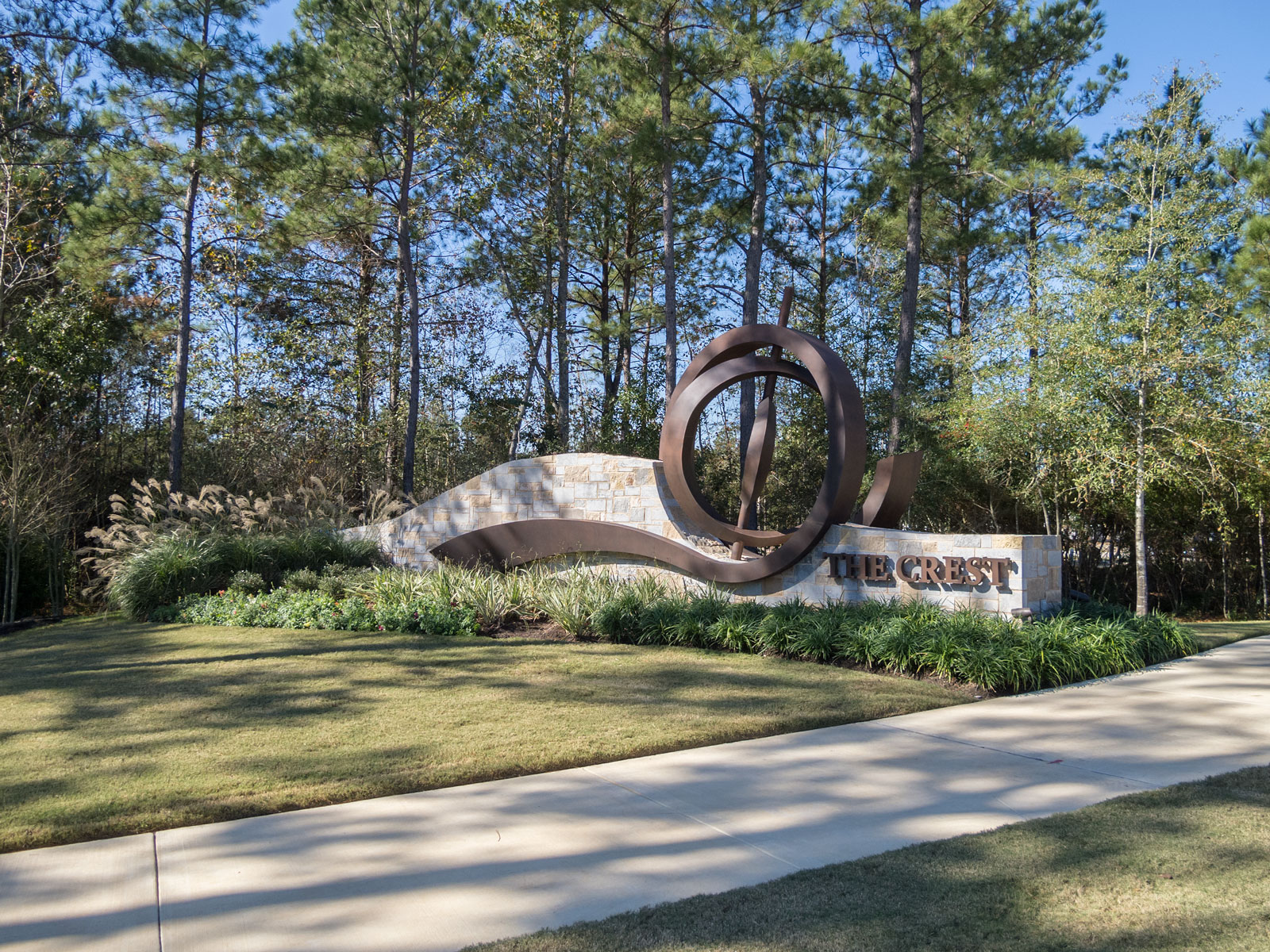 Corner view of entry monument with internally illuminated, custom fabricated aluminum sculptural element and halo-lit channel letters.
