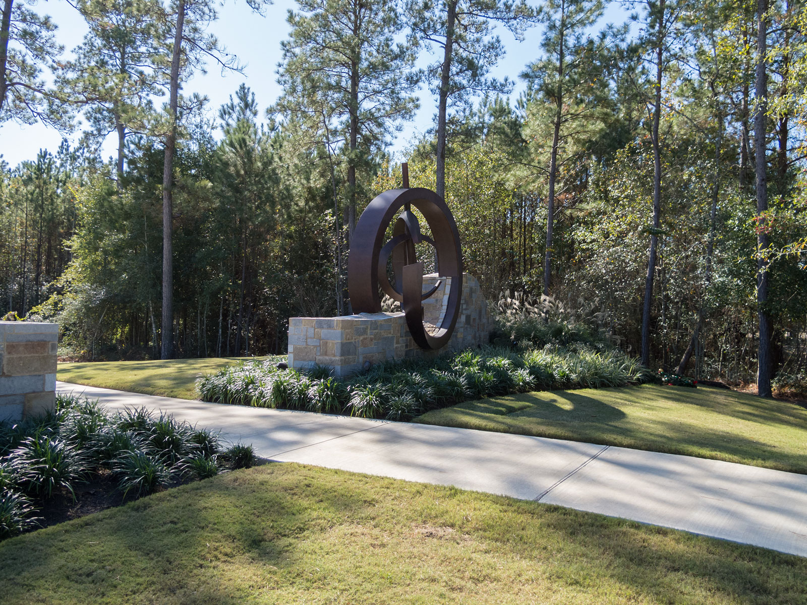 Back view of entry monument with internally illuminated, custom fabricated aluminum sculptural element and halo-lit channel letters.