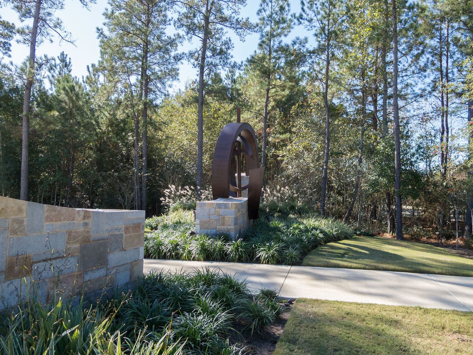 Side view of entry monument with internally illuminated, custom fabricated aluminum sculptural element and halo-lit channel letters.
