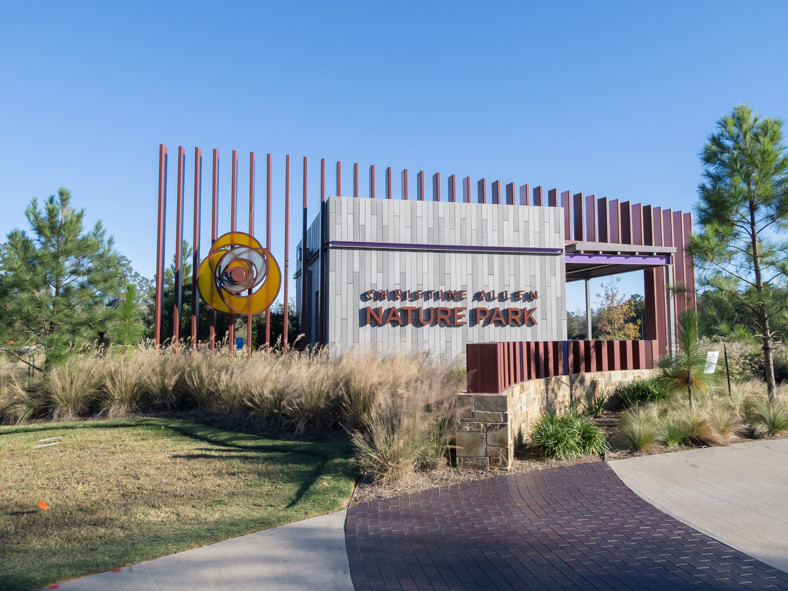 Front of building at Christine Allen Nature Park with custom halo-illuminated channel letters and fabricated rose with edge-lit 3Form petals.