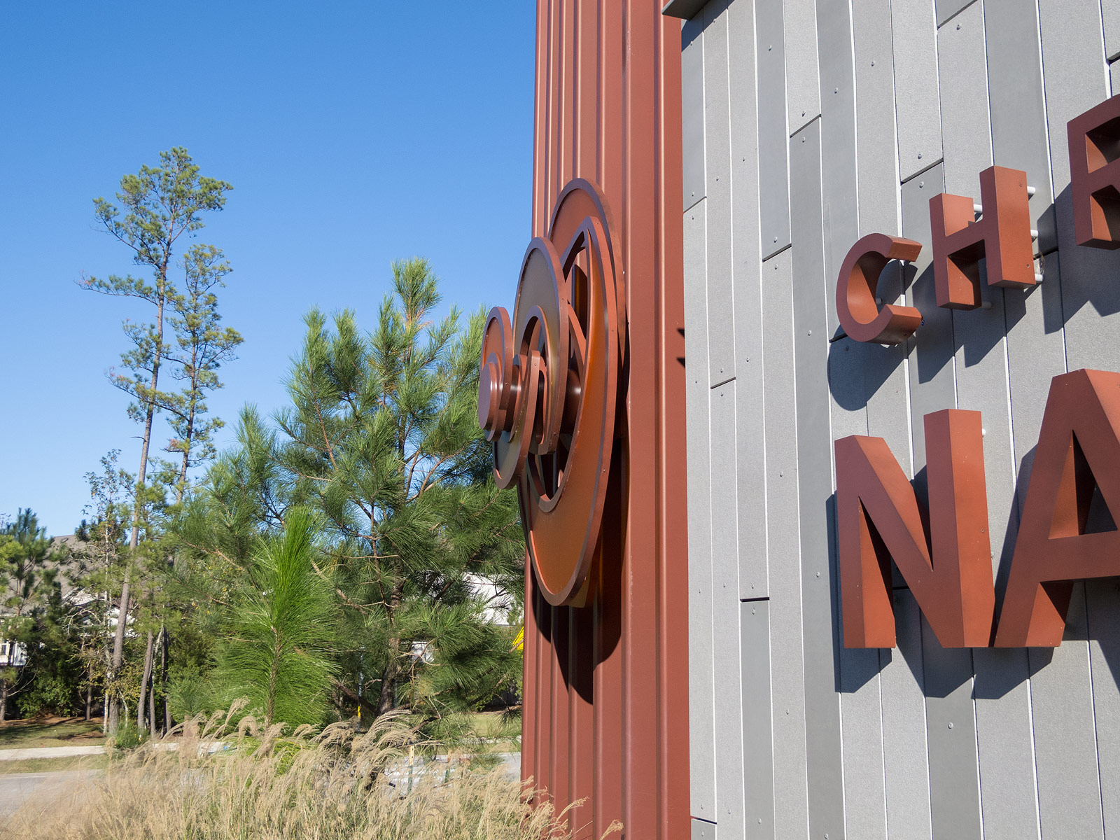 Close up view of halo-illuminated channel letters and fabricated rose sculpture with edge-lit 3Form petals.