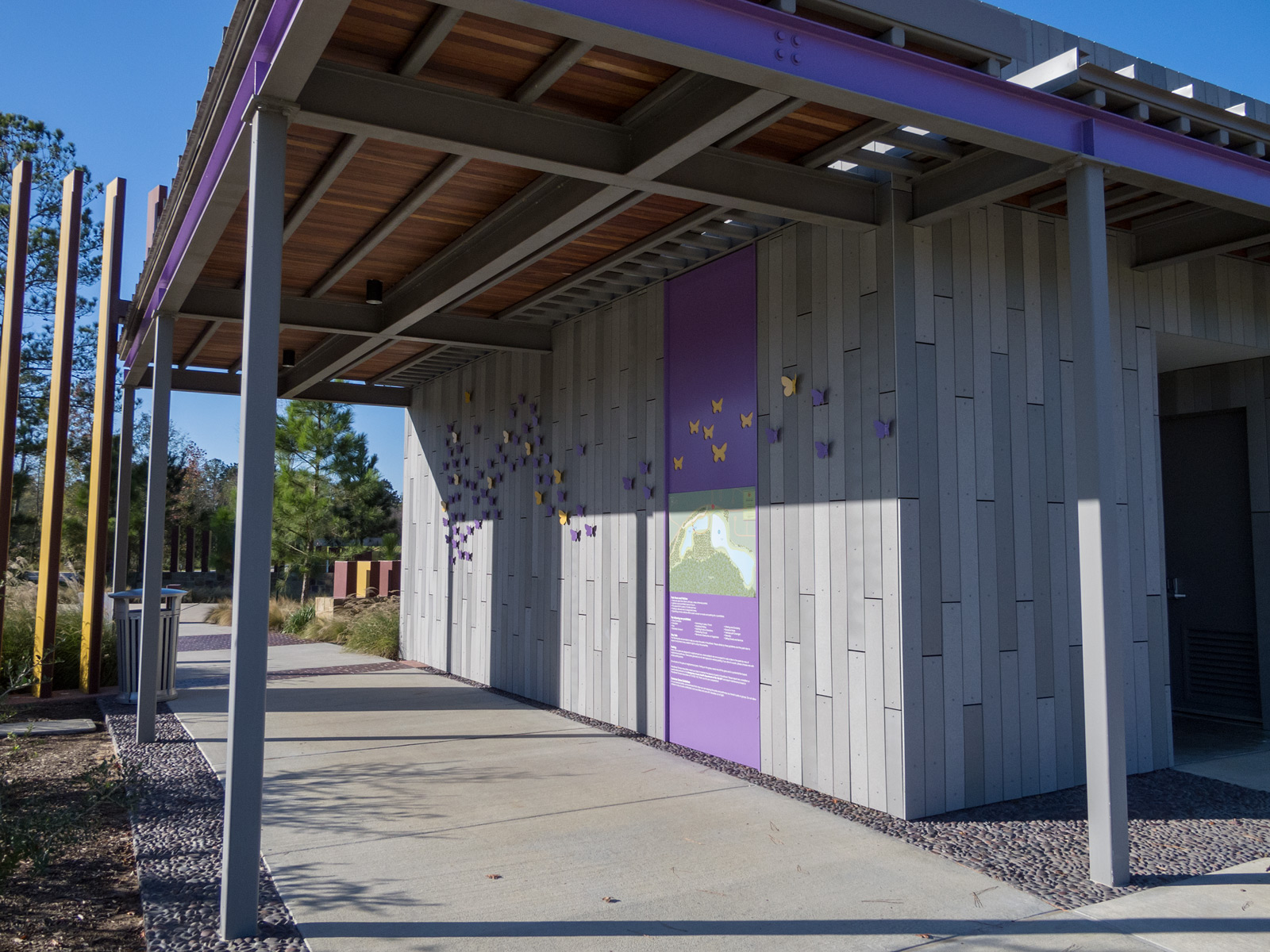 View from side of building with custom aluminum butterflies and park rules and map graphics panel.