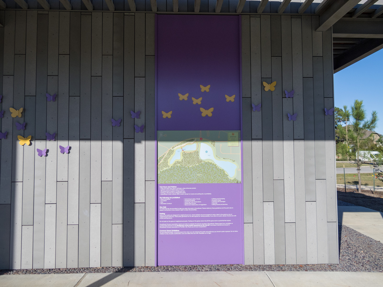 Close up view of park rules and map graphics panel and custom aluminum butterflies.