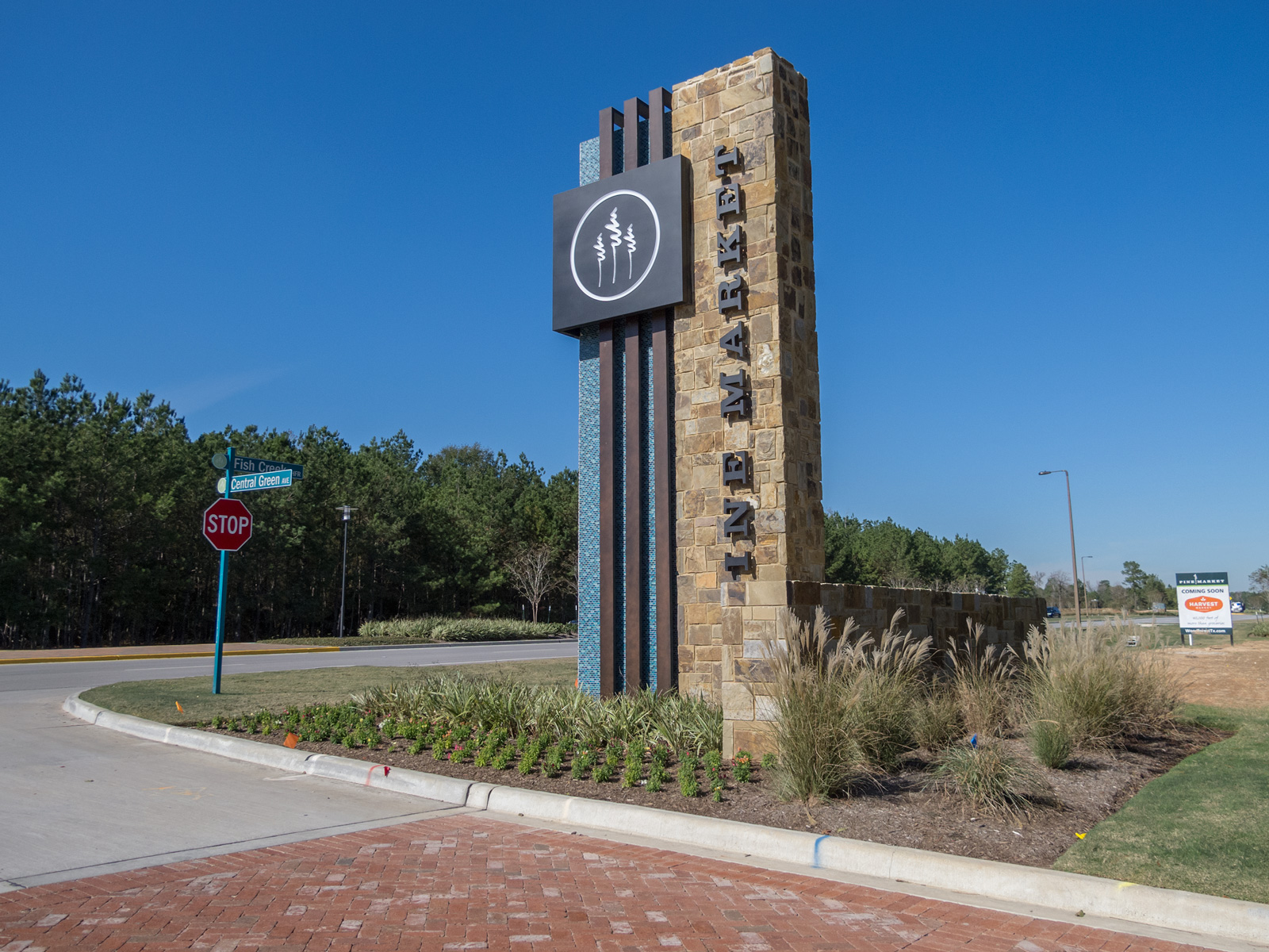 Custom fabricated monument with aluminum cabinet with illuminated push through graphics, halo-illuminated channel letters, and fabricated accent bands at Woodforest - Pine Market