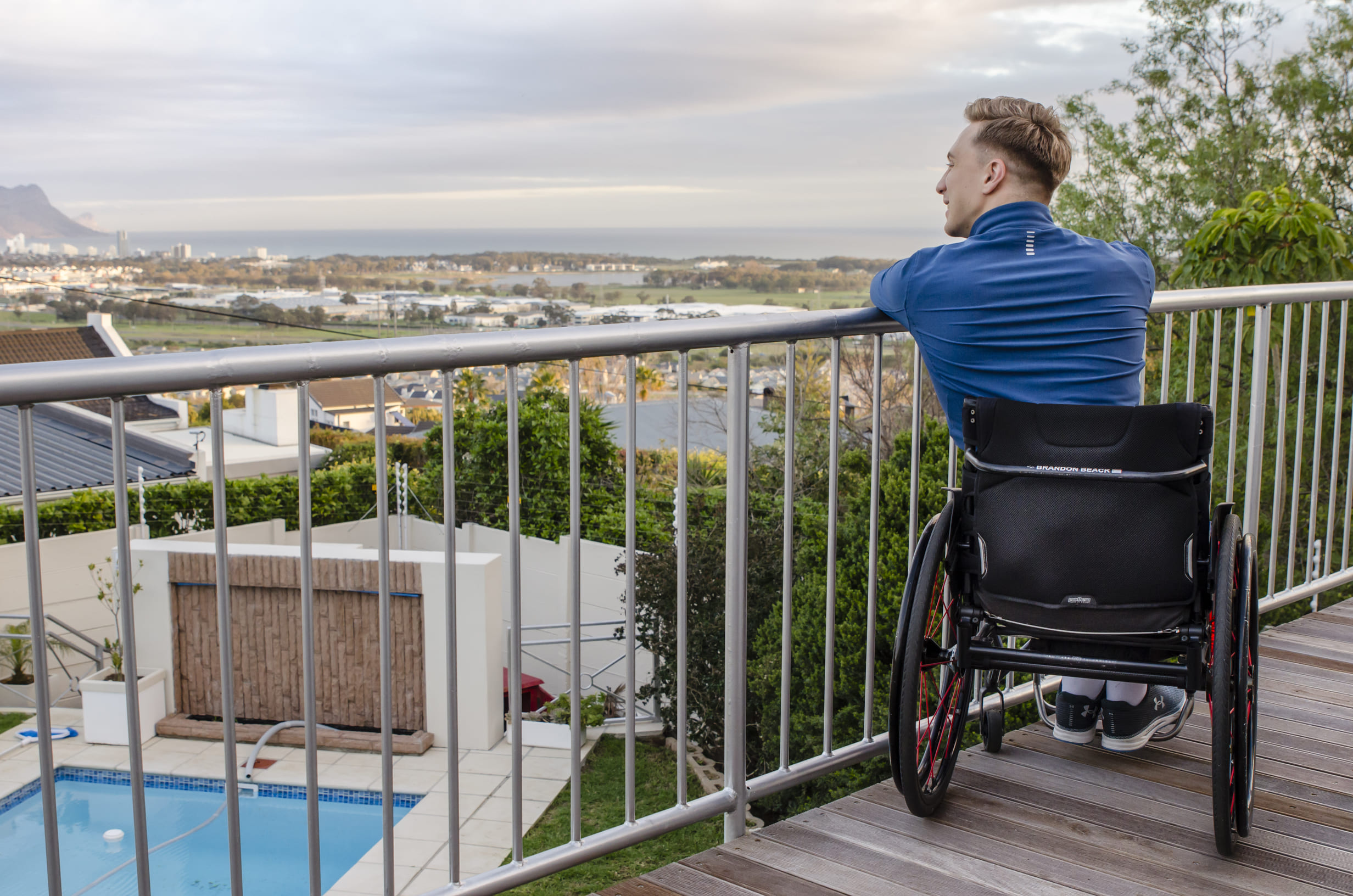 Portrait of Brandon Beack in his wheelchair overlooking the view from Somerset View Guest House balcony.