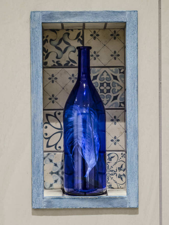 3 Way View bathroom detail photo of blue glass bottle inside wall frame and shelf