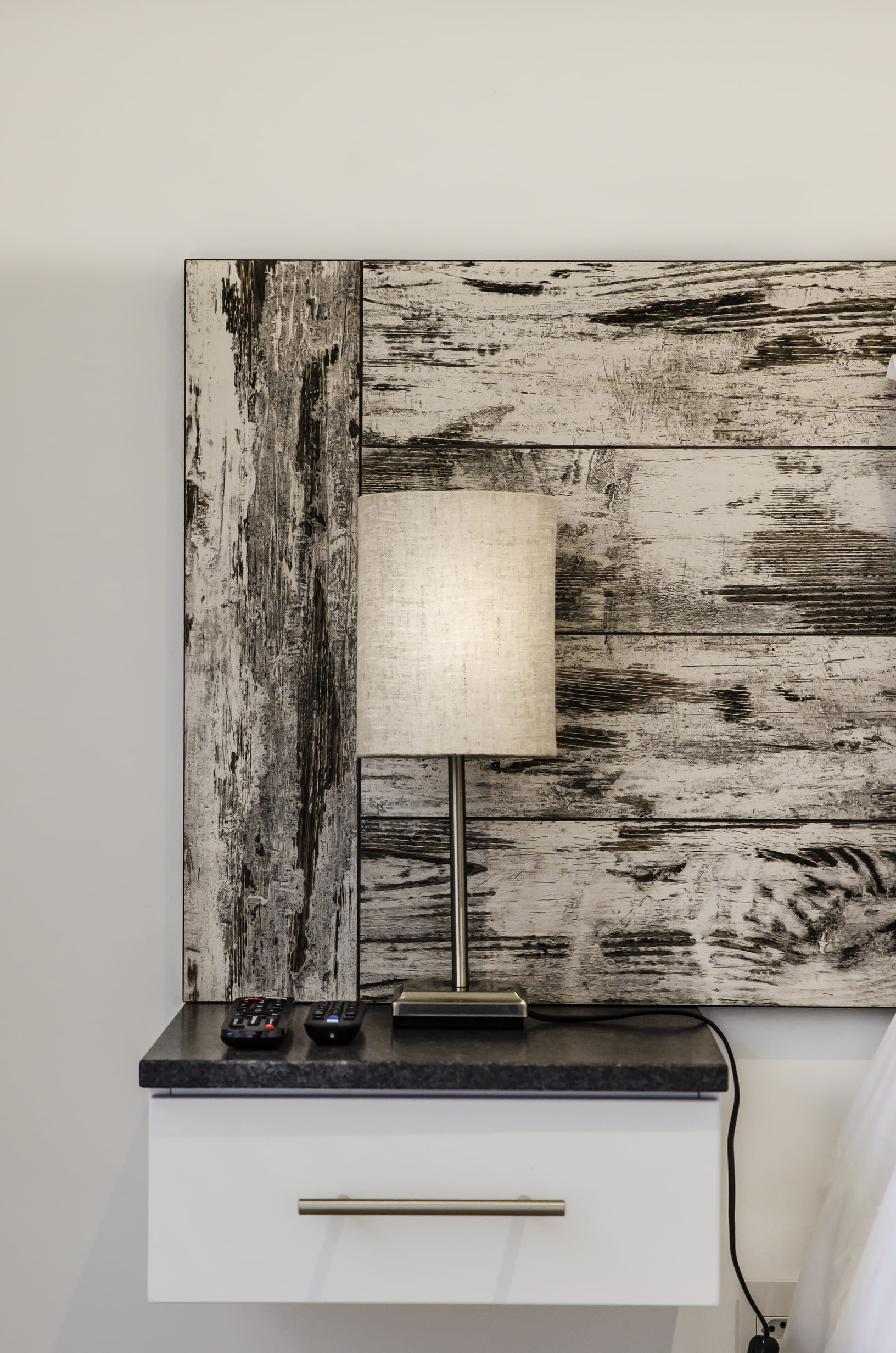 A View 4 You detail photo of floating bedside table, lamp and custom wooden headboard.