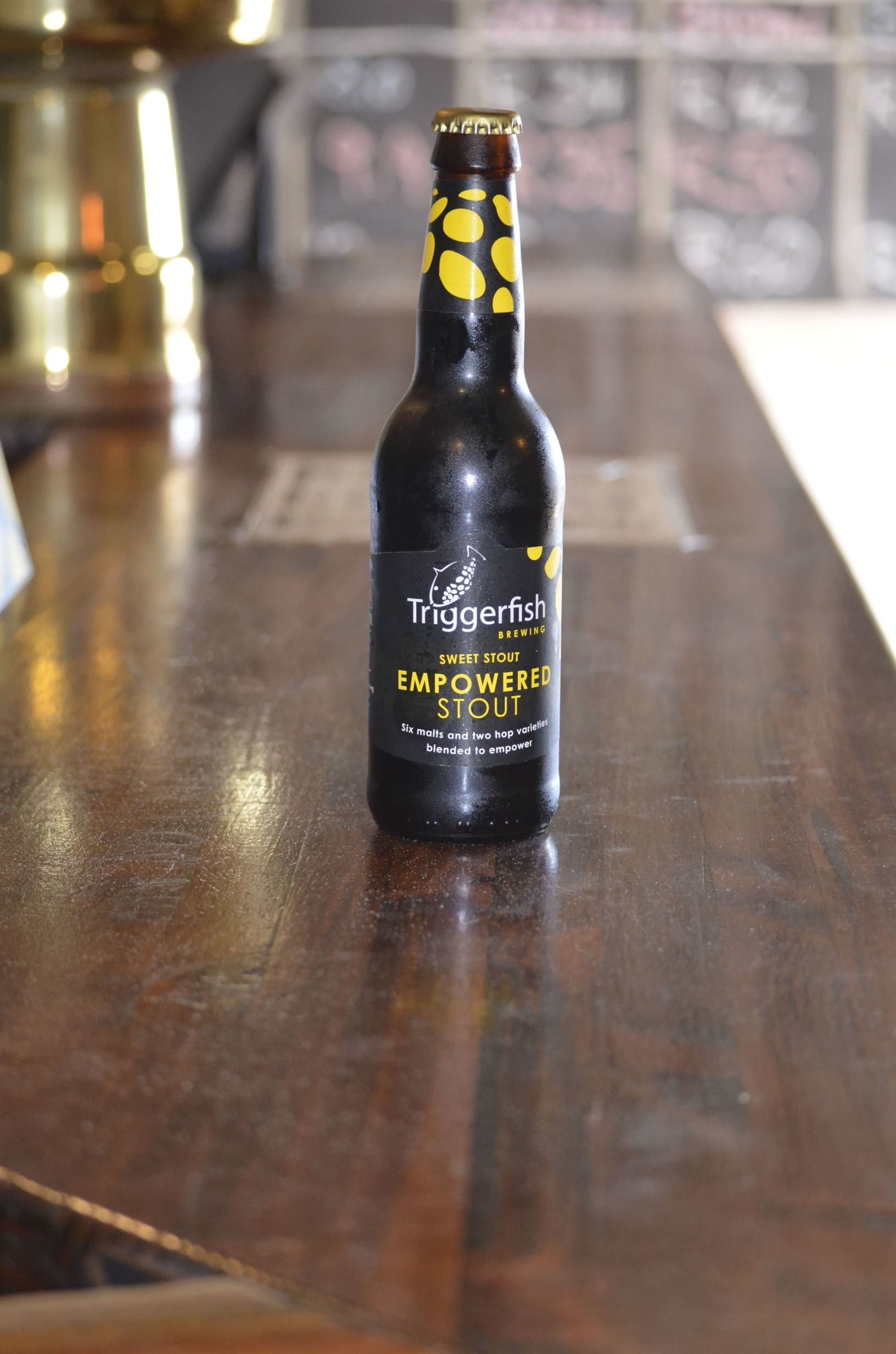 A closed bottle of Triggerfish beer on a wooden bar counter