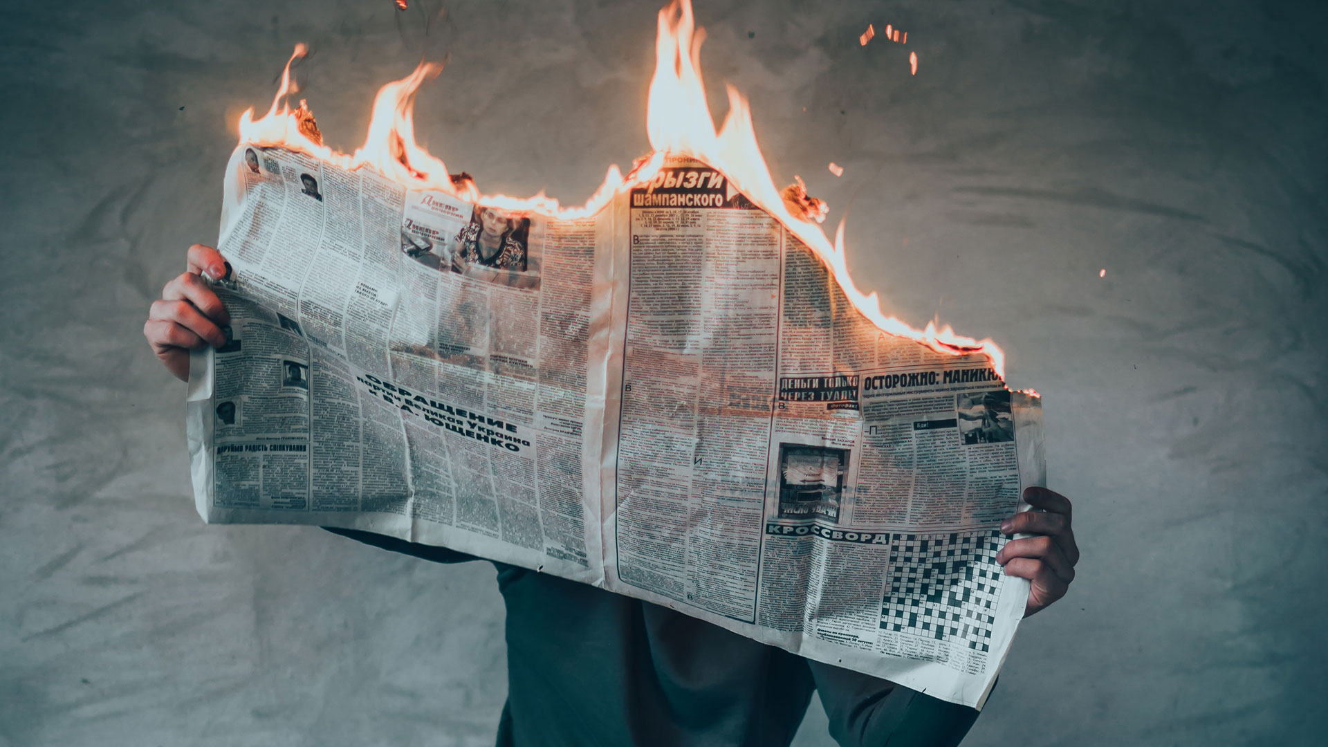 Article image shows a man who is holding a burning newspaper.