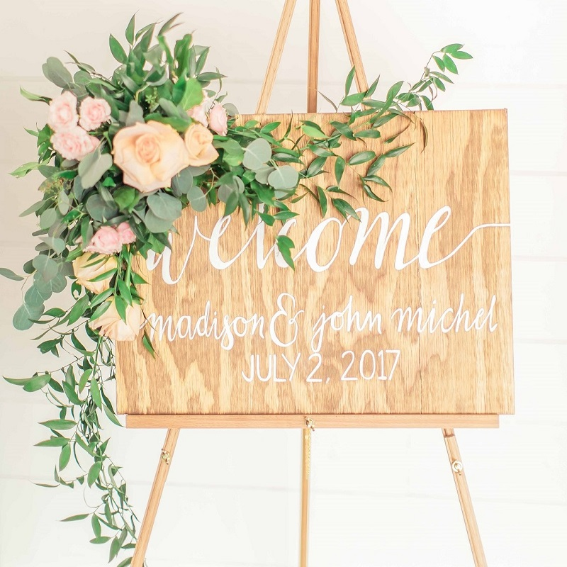 Wedding welcome sign with greenery and floral garland.