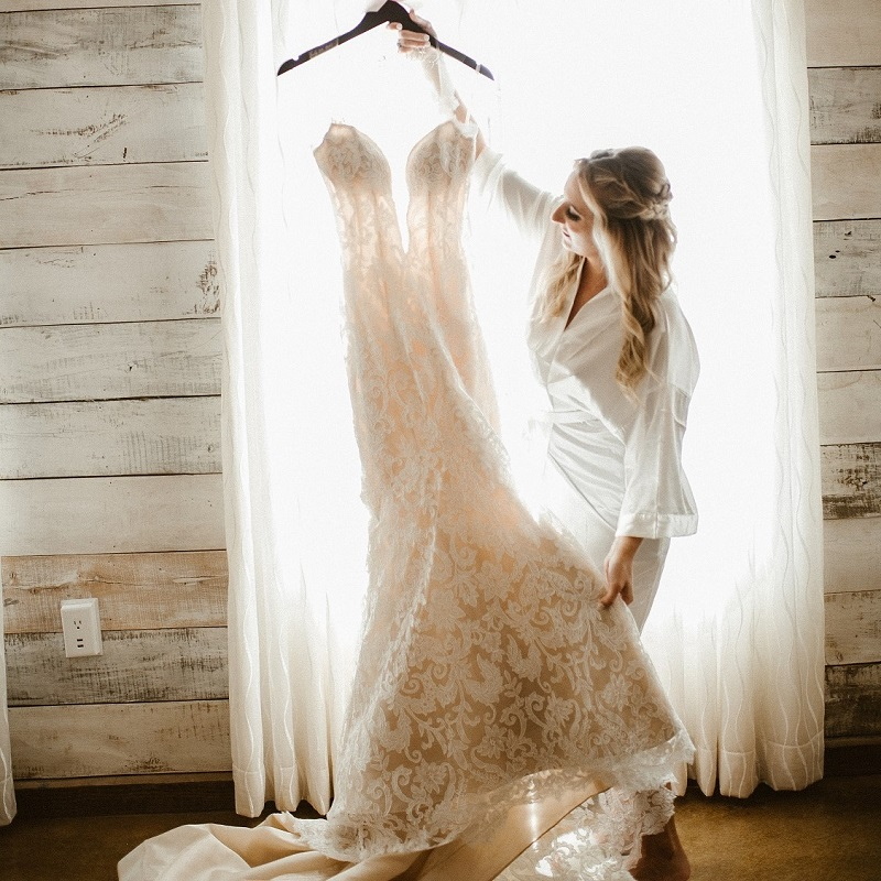 The bride holding her wedding dress.