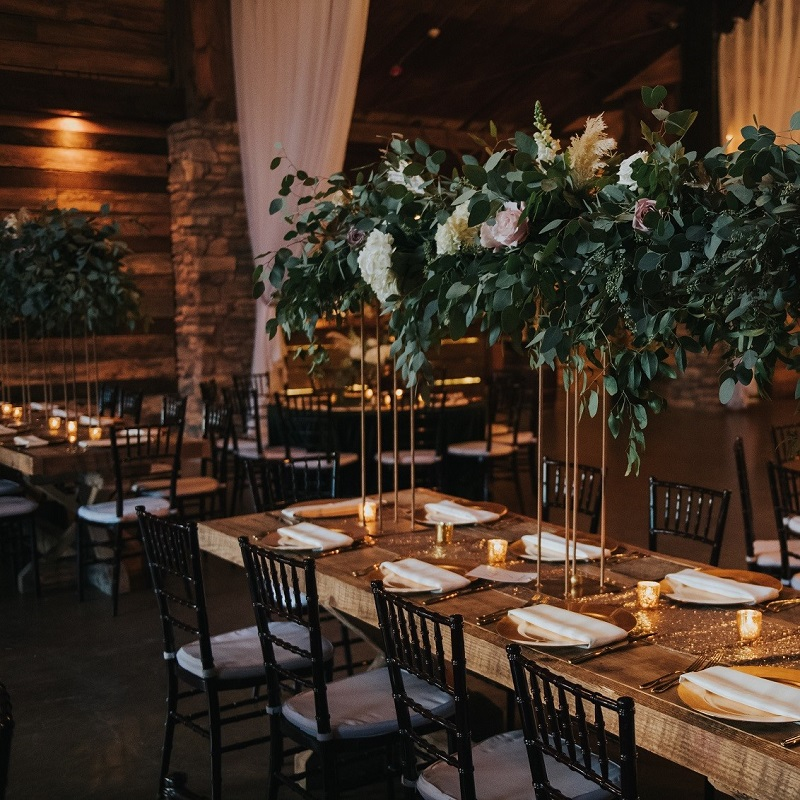 The farmhouse table and tall wedding centerpiece with cascading greenery.