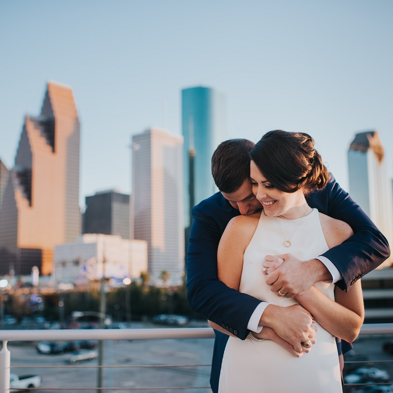 The bride and groom in front of downtown Houston skyline.