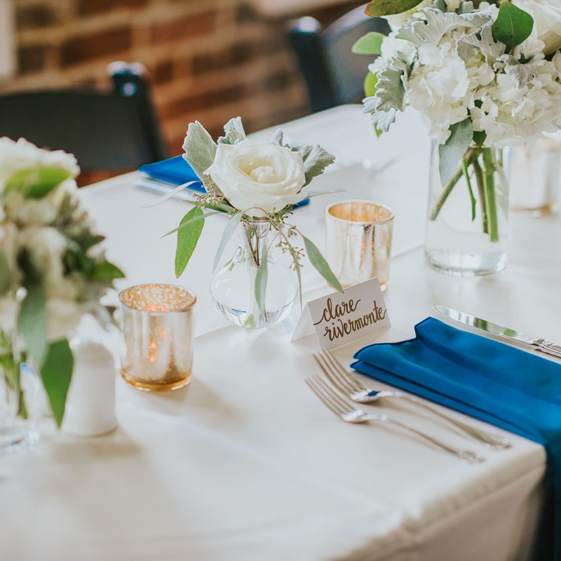 Simple and elegant wedding centerpiece with pop of blue napkin.