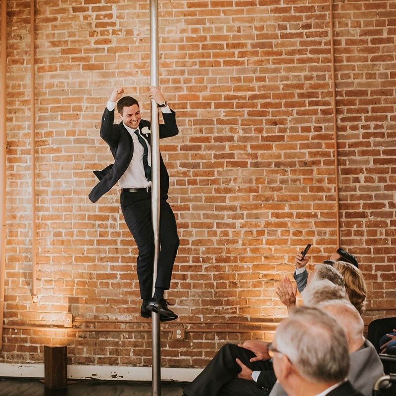 The groom coming down the fireman pole to the ceremony.