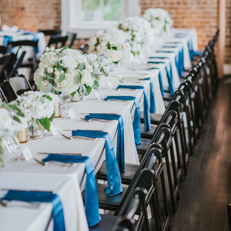 The long rectangle wedding table with ivory floral and blue napkins.