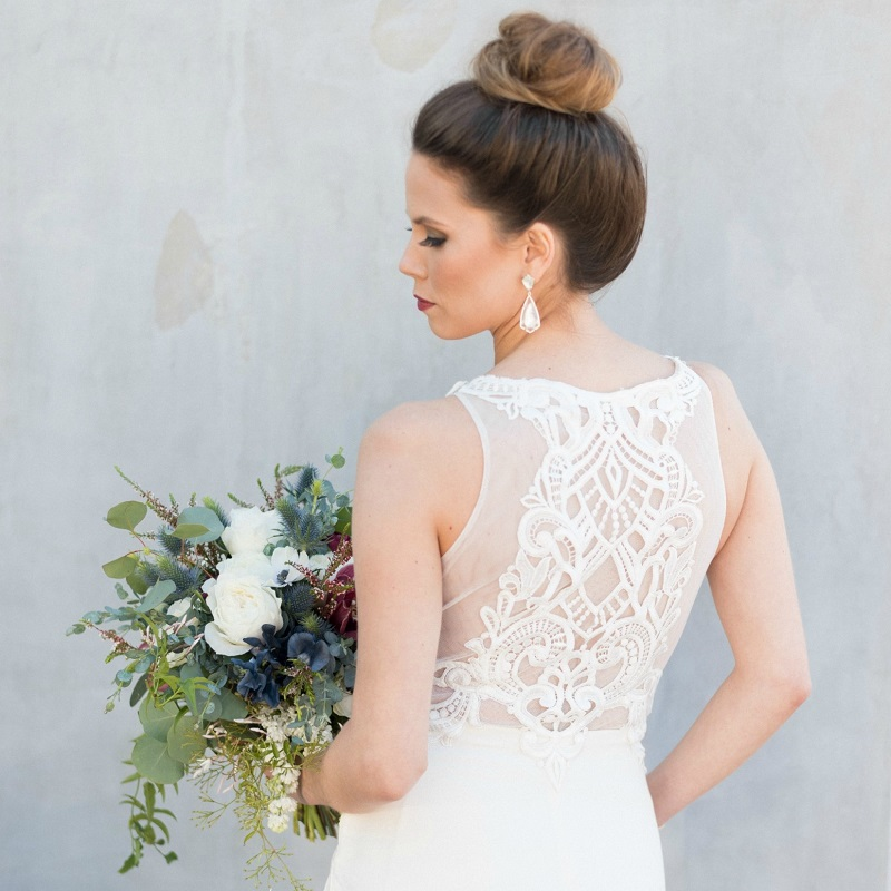 Detail shot of the back of the wedding dress and bouquet.