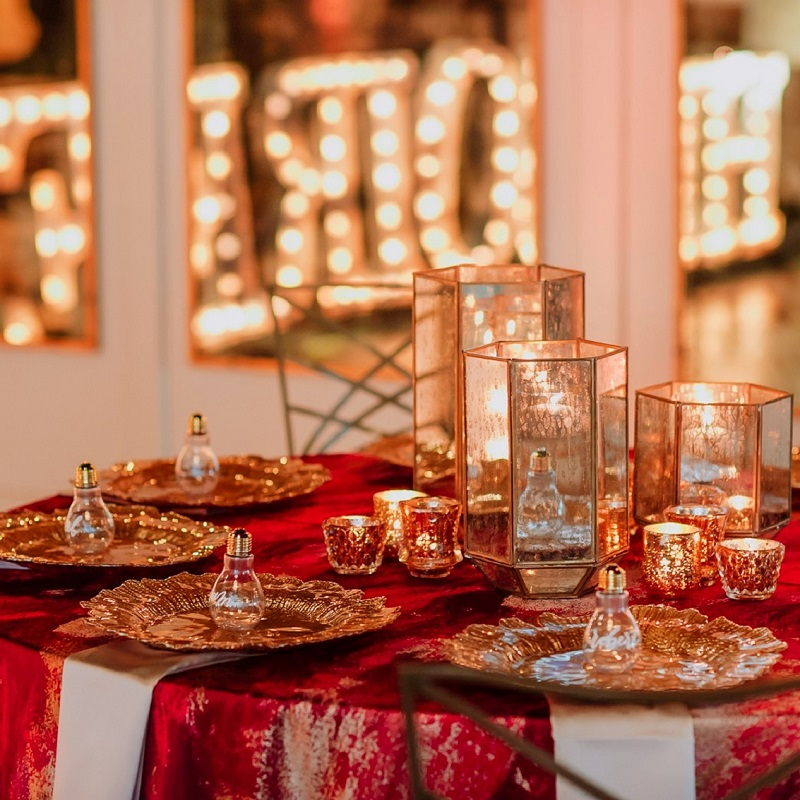 Red, burgundy and gold tablescape with marquee letters in the background.