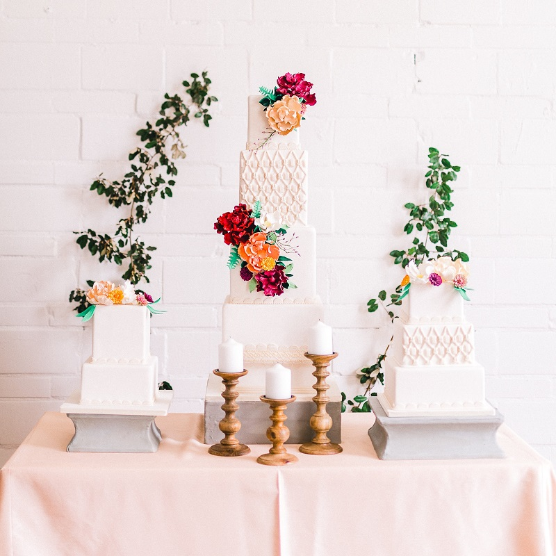 Model cakes with sugar flowers and greenery cascading on the wall.