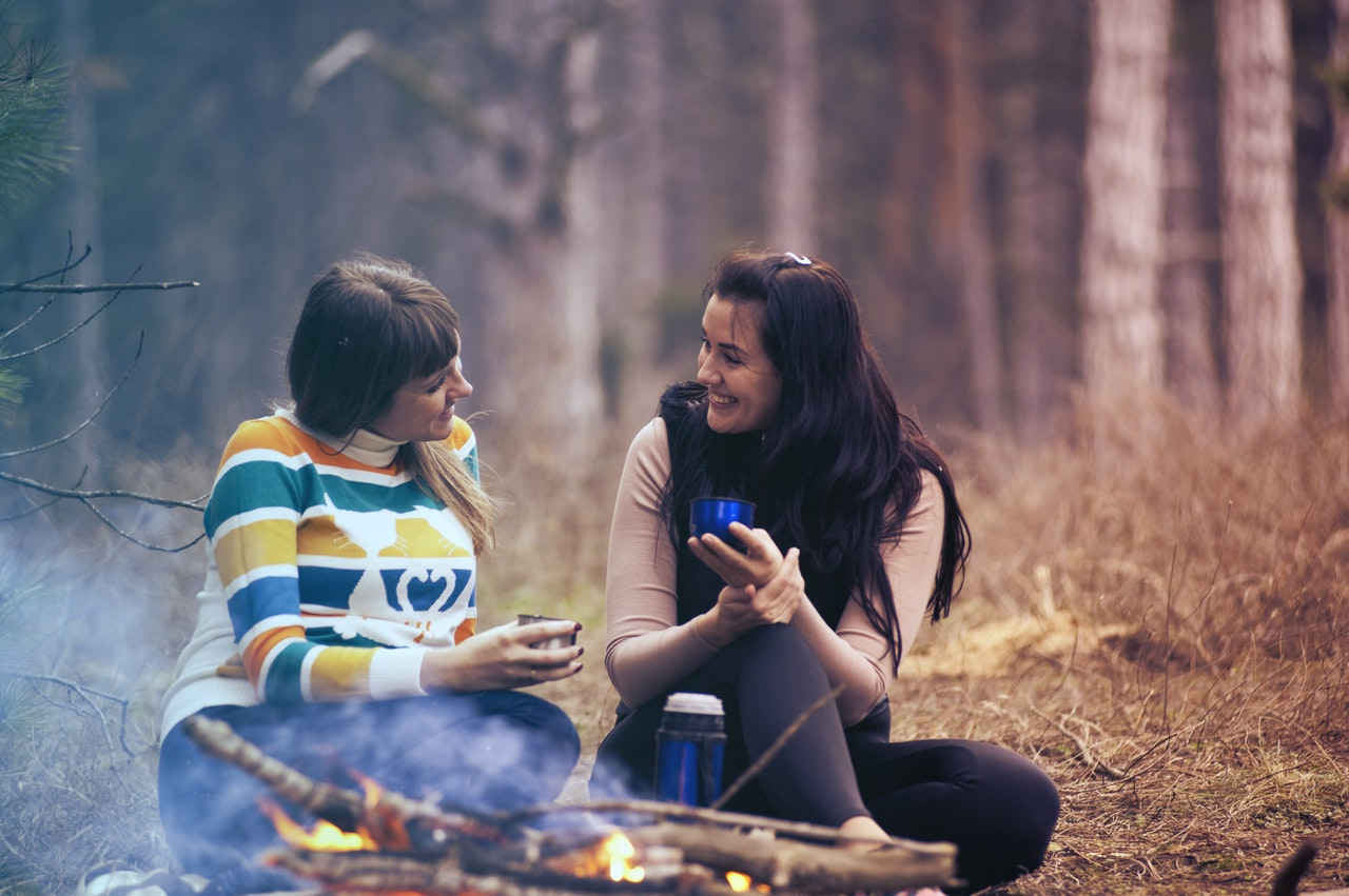 Two women sit together in a forest in the autumn, talking by a campfire