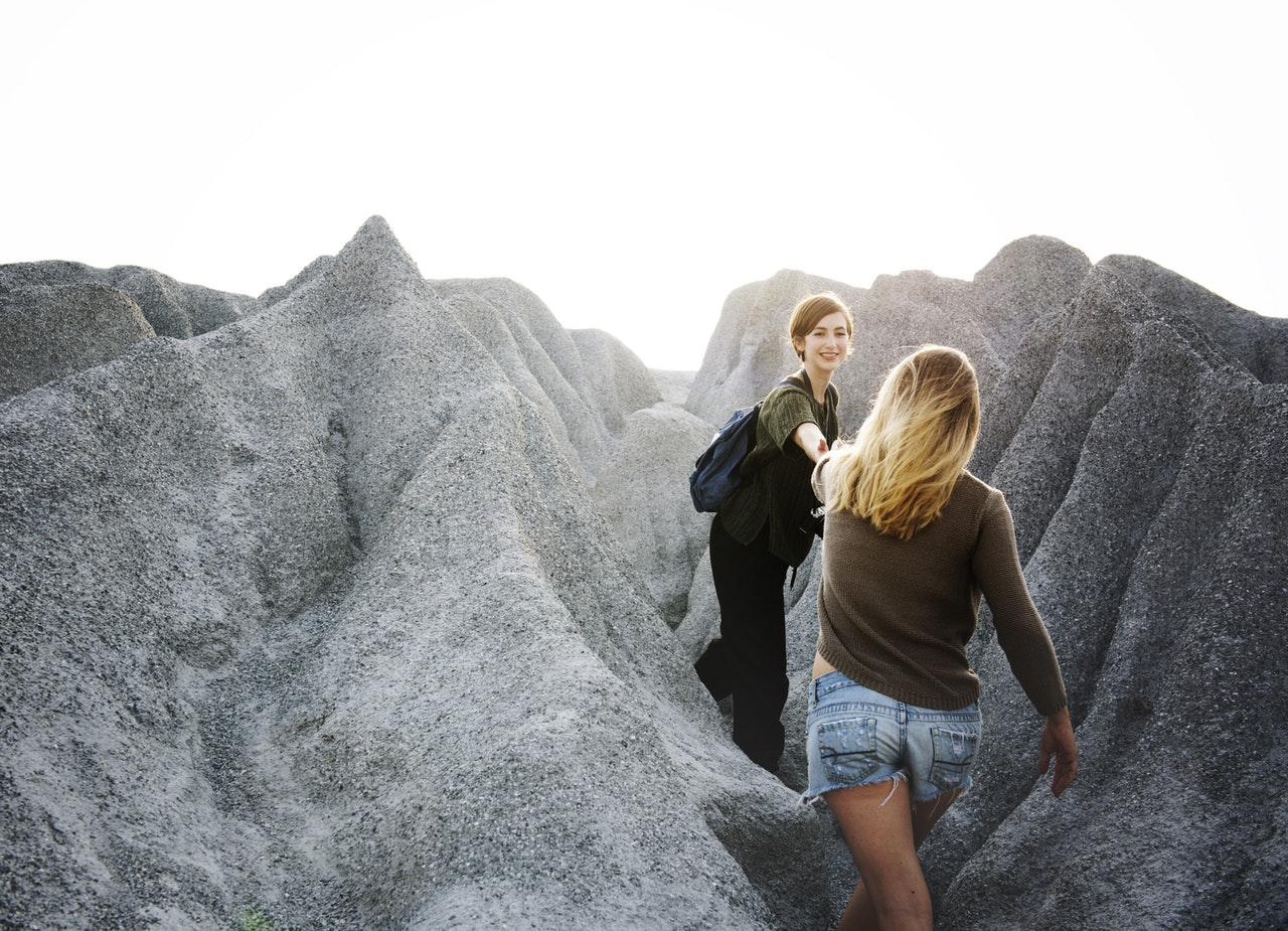 A photograph of two women hiking up a steep, rocky path. The woman in front turns around and extends her hand to help the woman behind her