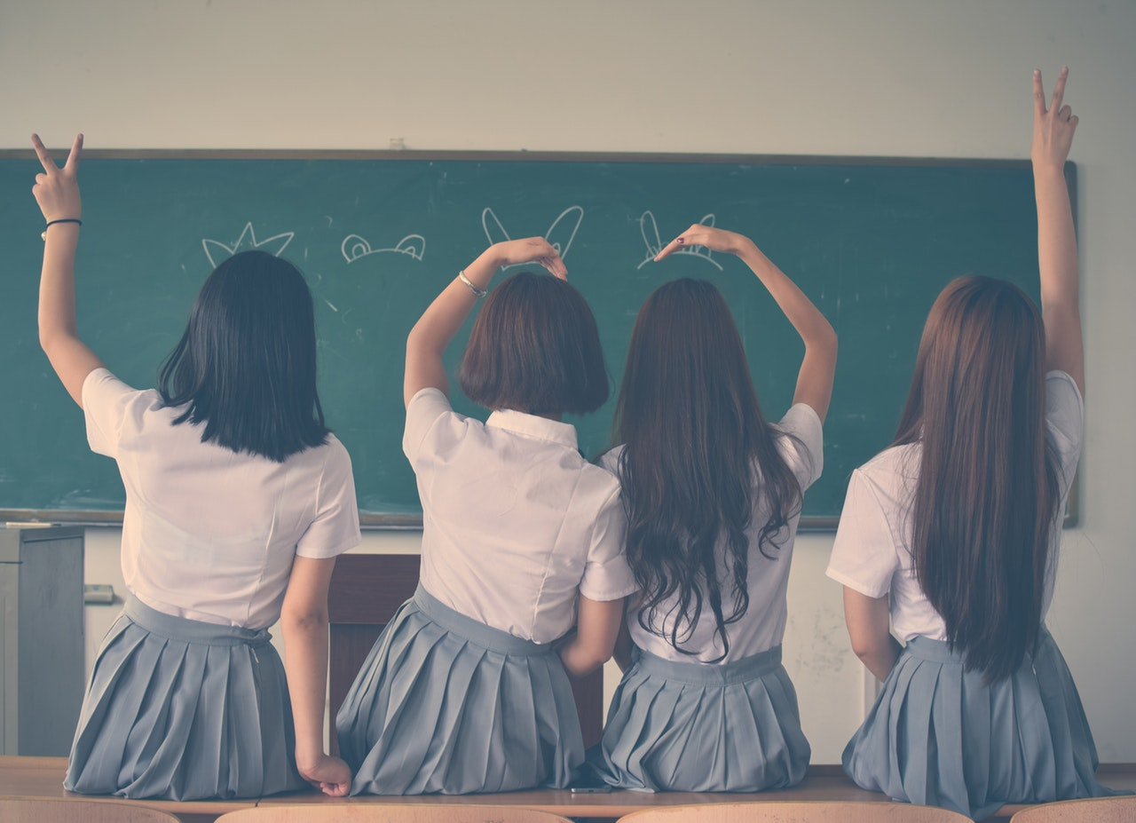 Four girls with brown hair wearing school uniforms lean against a desk with their backs to the camera, facing a chalkboard.