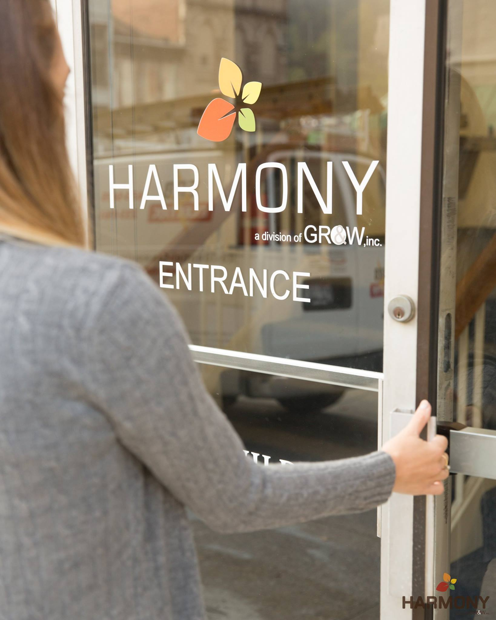 A woman with long dark blonde hair wearing a gray sweater opens the door to a harmony clinic in west virginia.