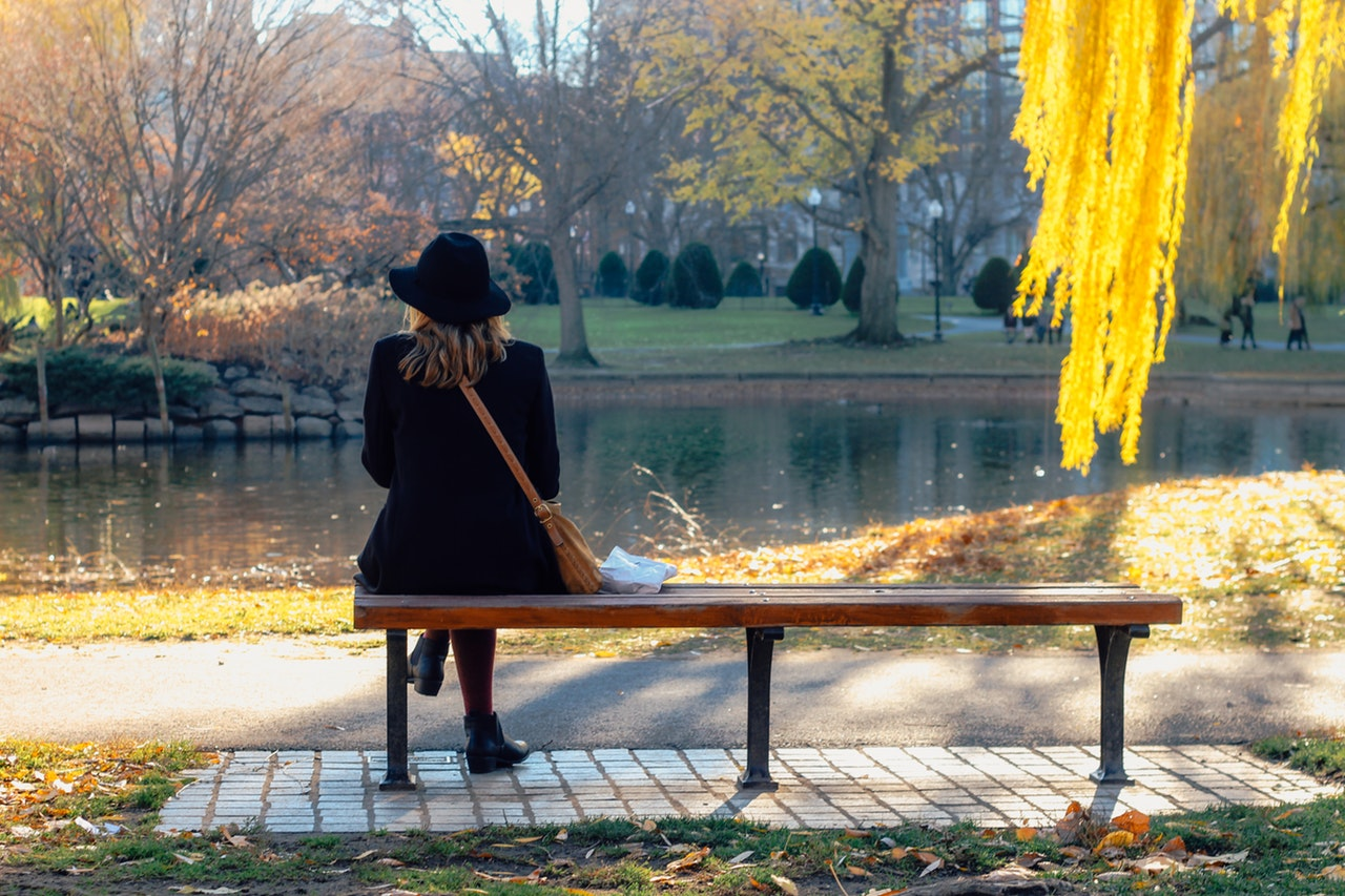 A woman in a black jacket and hat with a brown cross-body purse sits on a park bench in autumn, looking out over a pond.