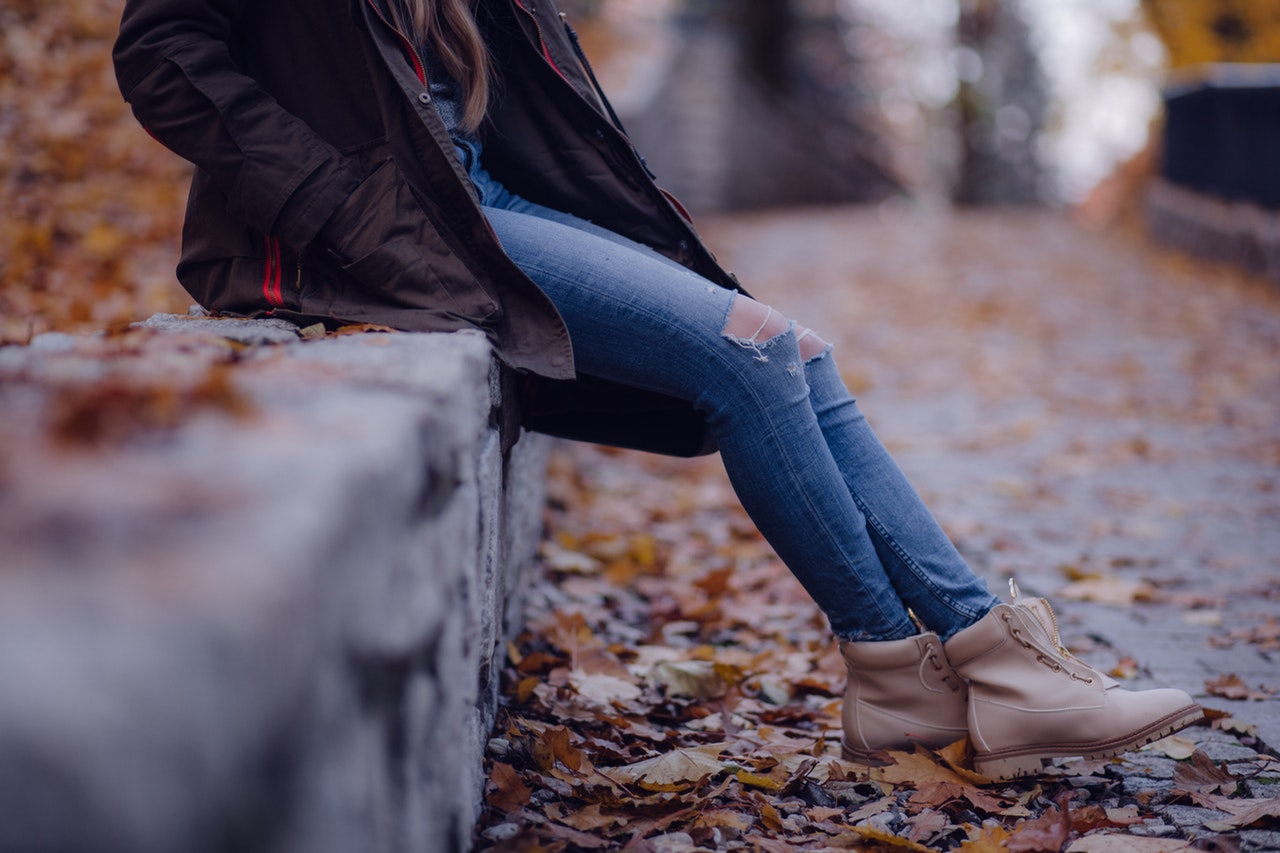 A young woman wearing jeans, a dark jacket, and brown boots leans against a stone wall along a road covered in orange fallen leaves.