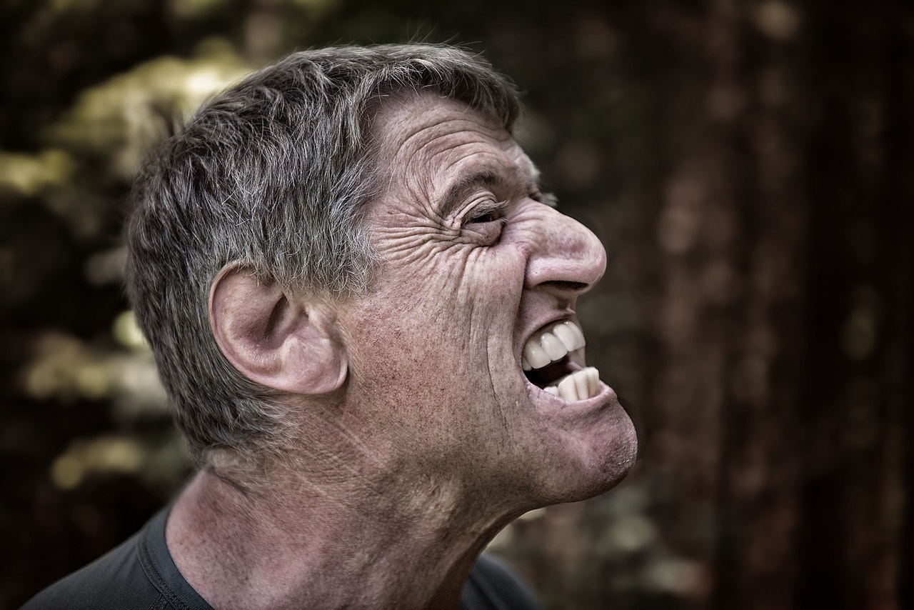 a man with graying hair in profile, his face scrunched up in anger