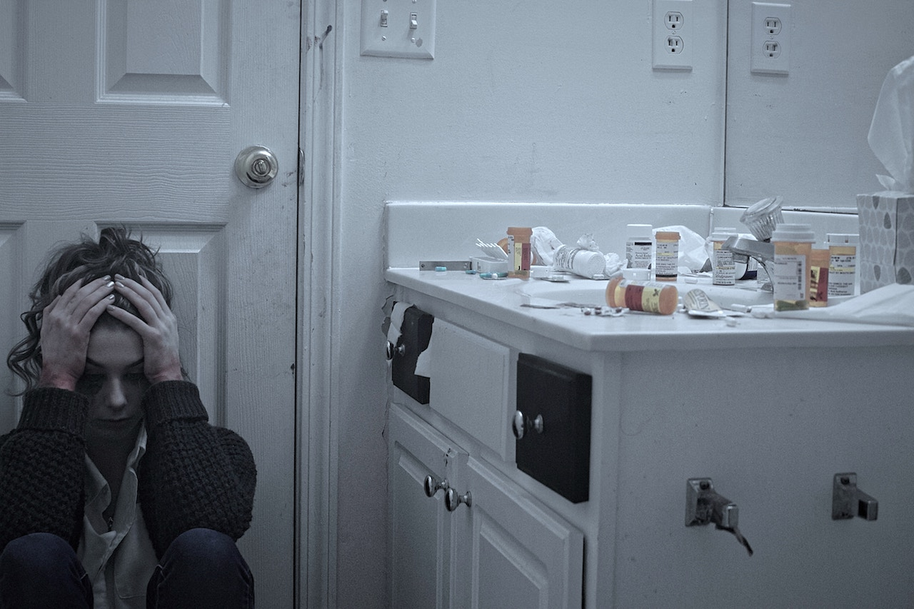 sad addicted woman with pill bottles on counter